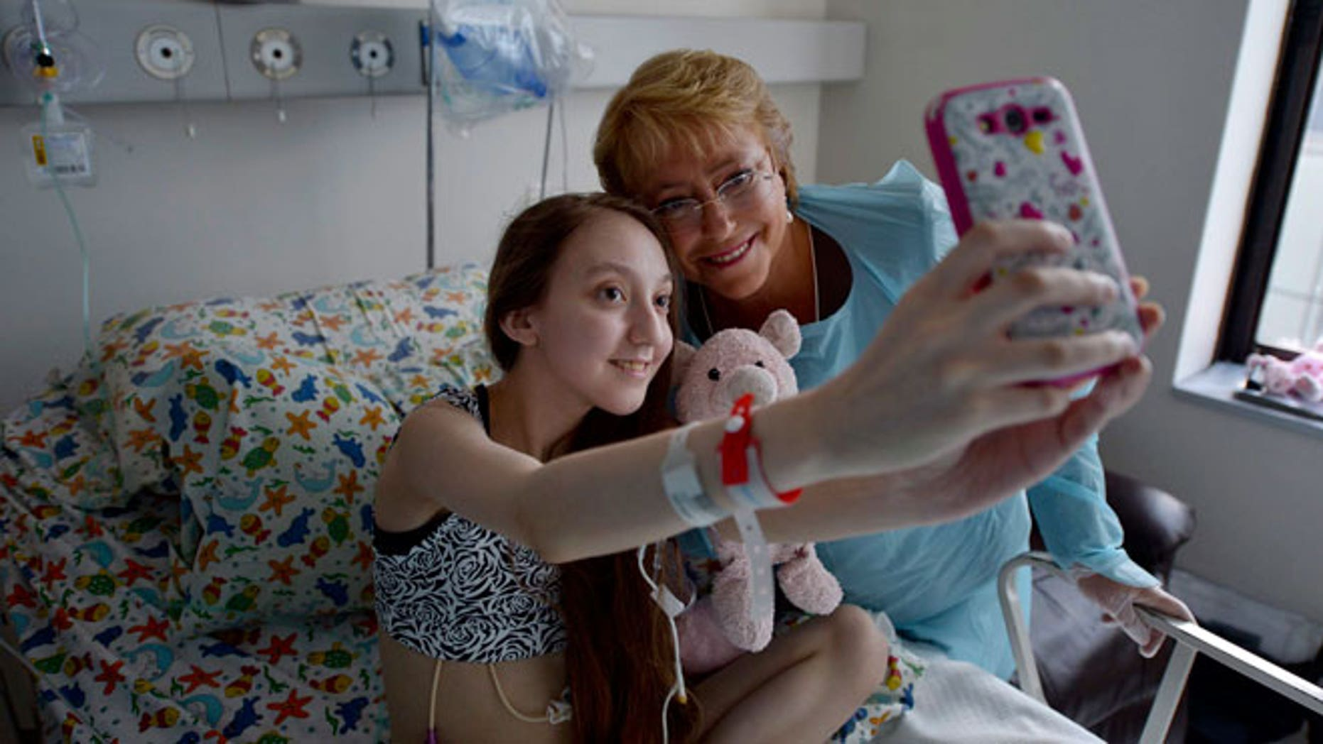 Chile President Michelle Bachelet, right, poses for a selfie with Valentina Maureira, who suffers from cystic fibrosis, at a hospital in Santiago, Chile, Saturday, Feb. 28, 2015.