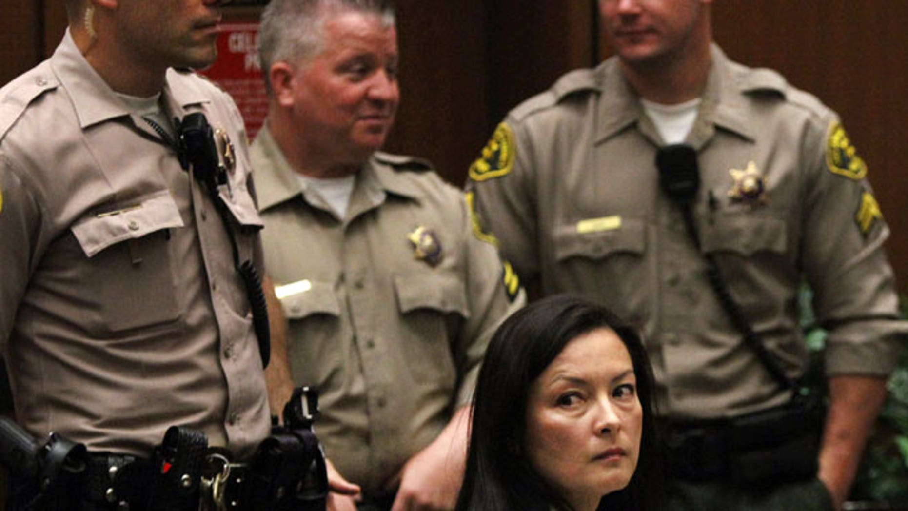 In this May 15, 2013 file photo, Kelly Soo Park looks back at the gallery as opening motions are made in her murder trial. Park was then charged with the 2008 killing of aspiring model and actress Juliana Redding. Los Angeles prosecutors say Park and Dr. Munir Uwaydah are both charged in a conspiracy to fraudulently bill insurance companies $150 million.