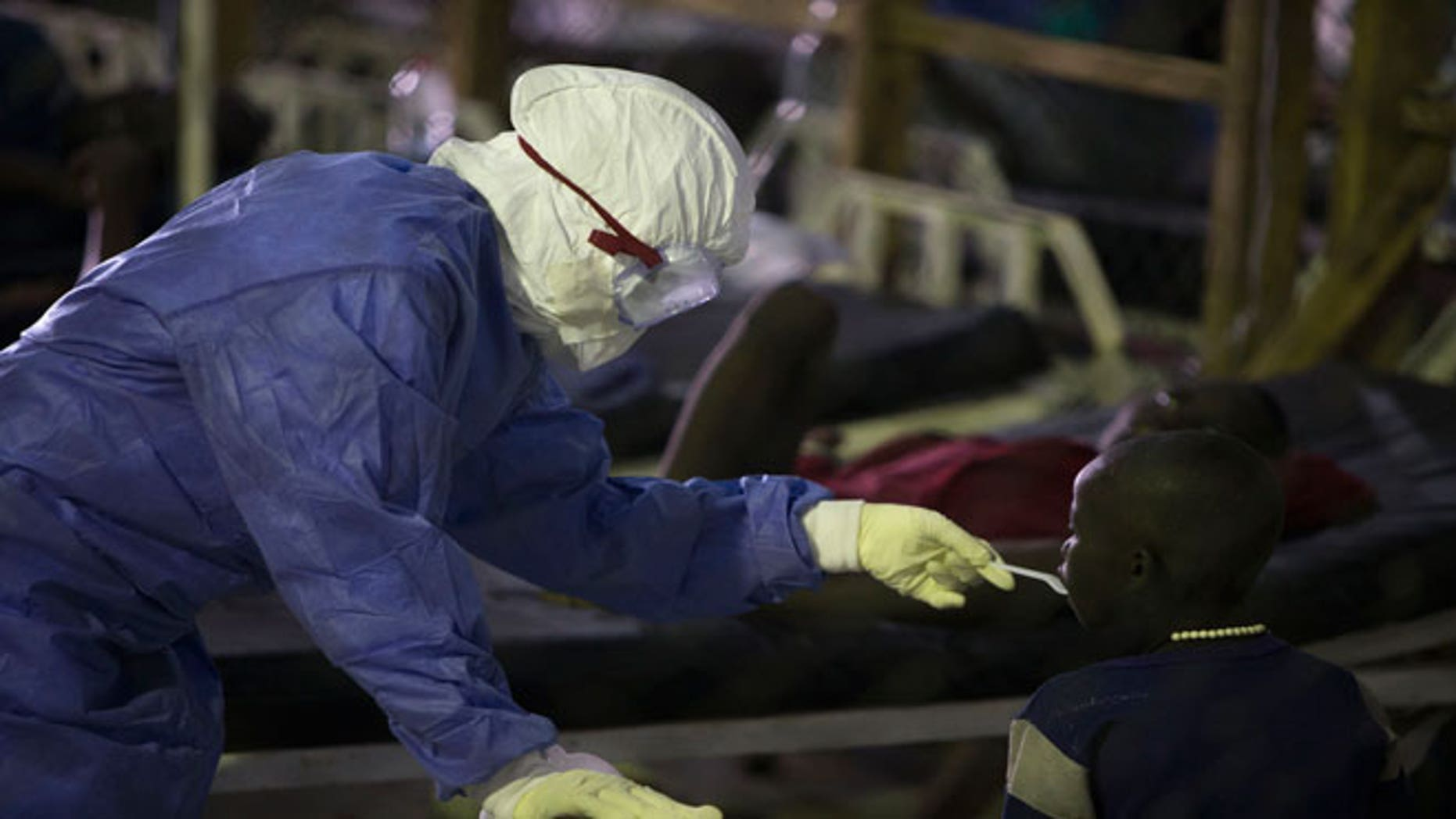 A health worker wearing protective equipment feeds a patient being treated for Ebola at the Island Clinic in Monrovia, September 30, 2014.