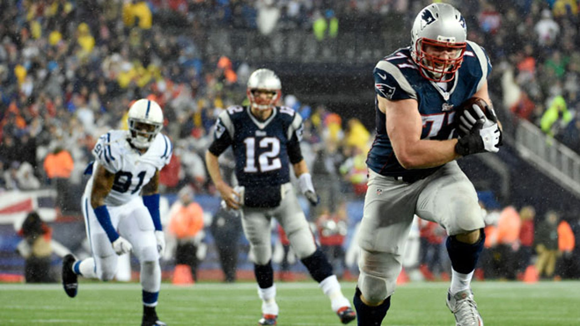 Jan 18, 2015; Foxborough, MA, USA; New England Patriots tackle Nate Solder (77) catches a pass from quarterback Tom Brady (12) and runs for a touchdown against the Indianapolis Colts in the third quarter in the AFC Championship Game at Gillette Stadium.