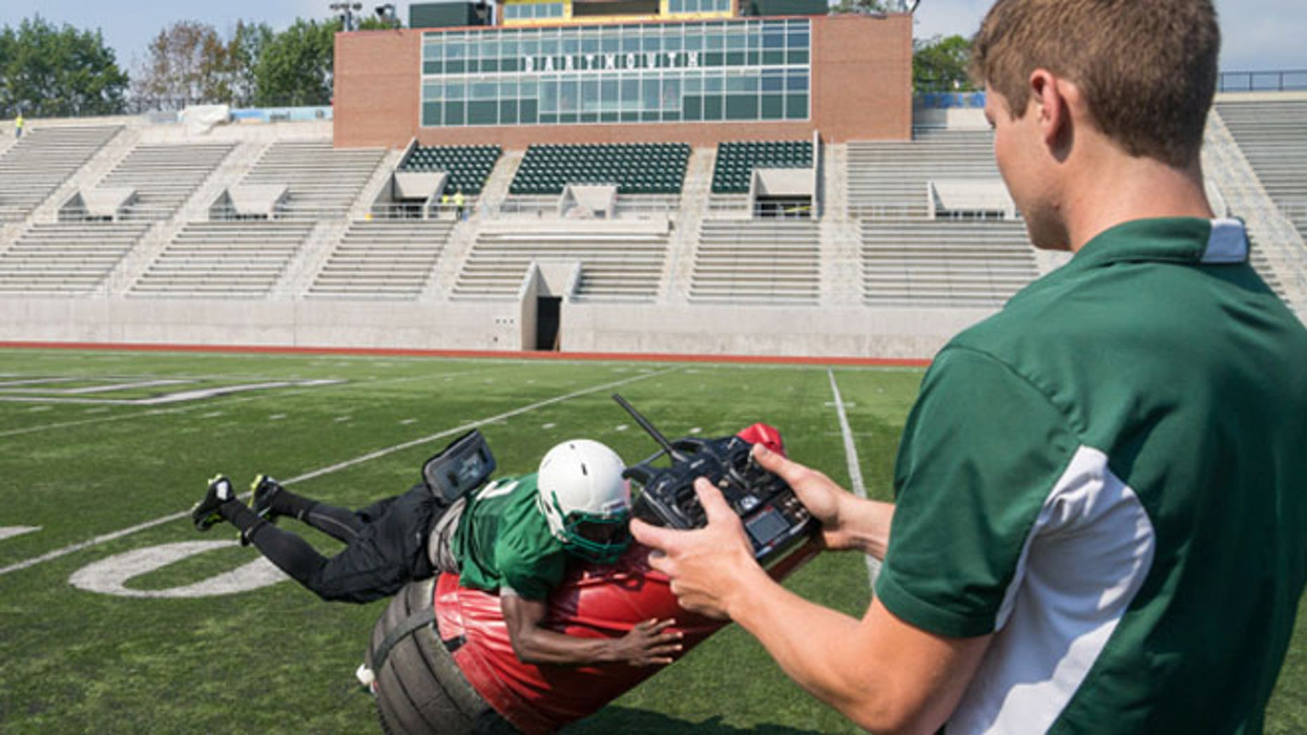 Victor Williams '16 tackles the Mobile Virtual Player, which he and his teammates will use at practice. Quinn Connell '13, Thayer '14, controls the device, which he and other Thayer engineers helped develop.