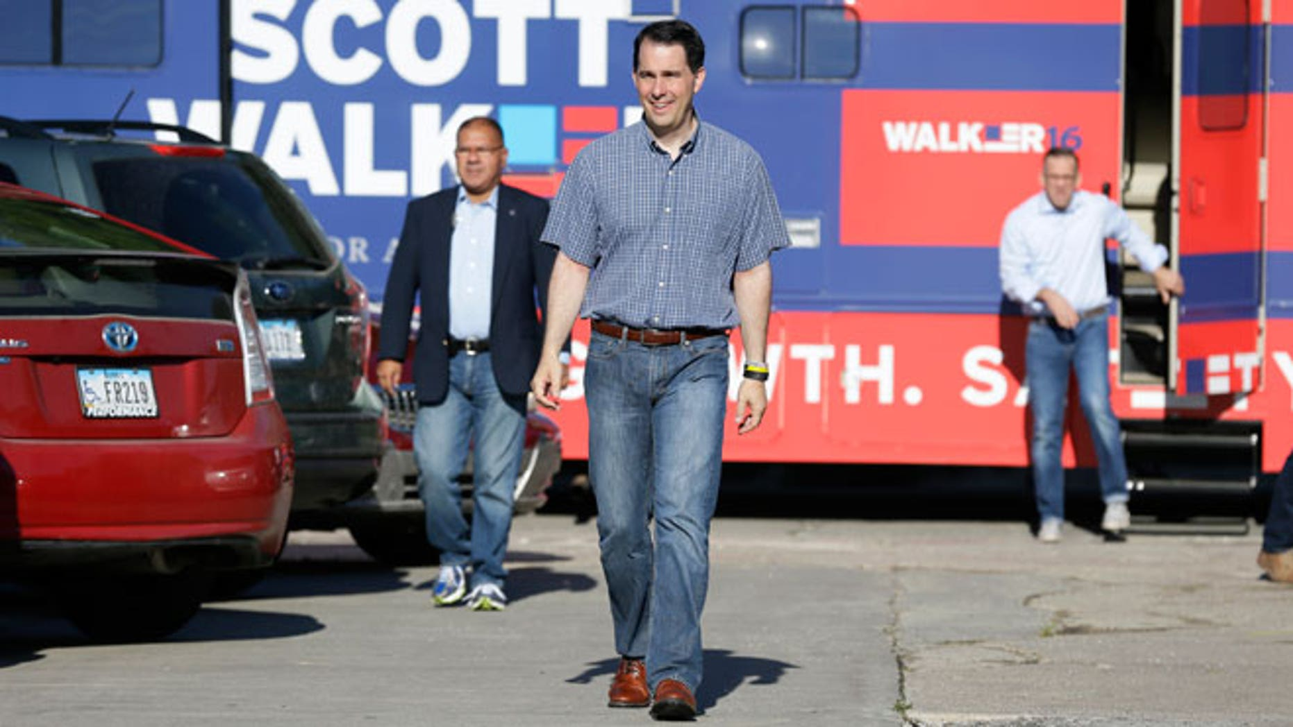 "In this July 31, 2015, file photo, Republican presidential candidate Wisconsin Gov. Scott Walker walks from his campaign bus to meet with local residents at Tom and Tiff's diner, in Glenwood, Iowa. Walker is counting steps on his FitBit. Jeb Bush swears by a paleo diet. Bobby Jindal is a self-proclaimed ""gym rat."" With long travel days and a fresh slab of cherry pie never far away, the campaign trail is a notoriously unhealthy place to live."