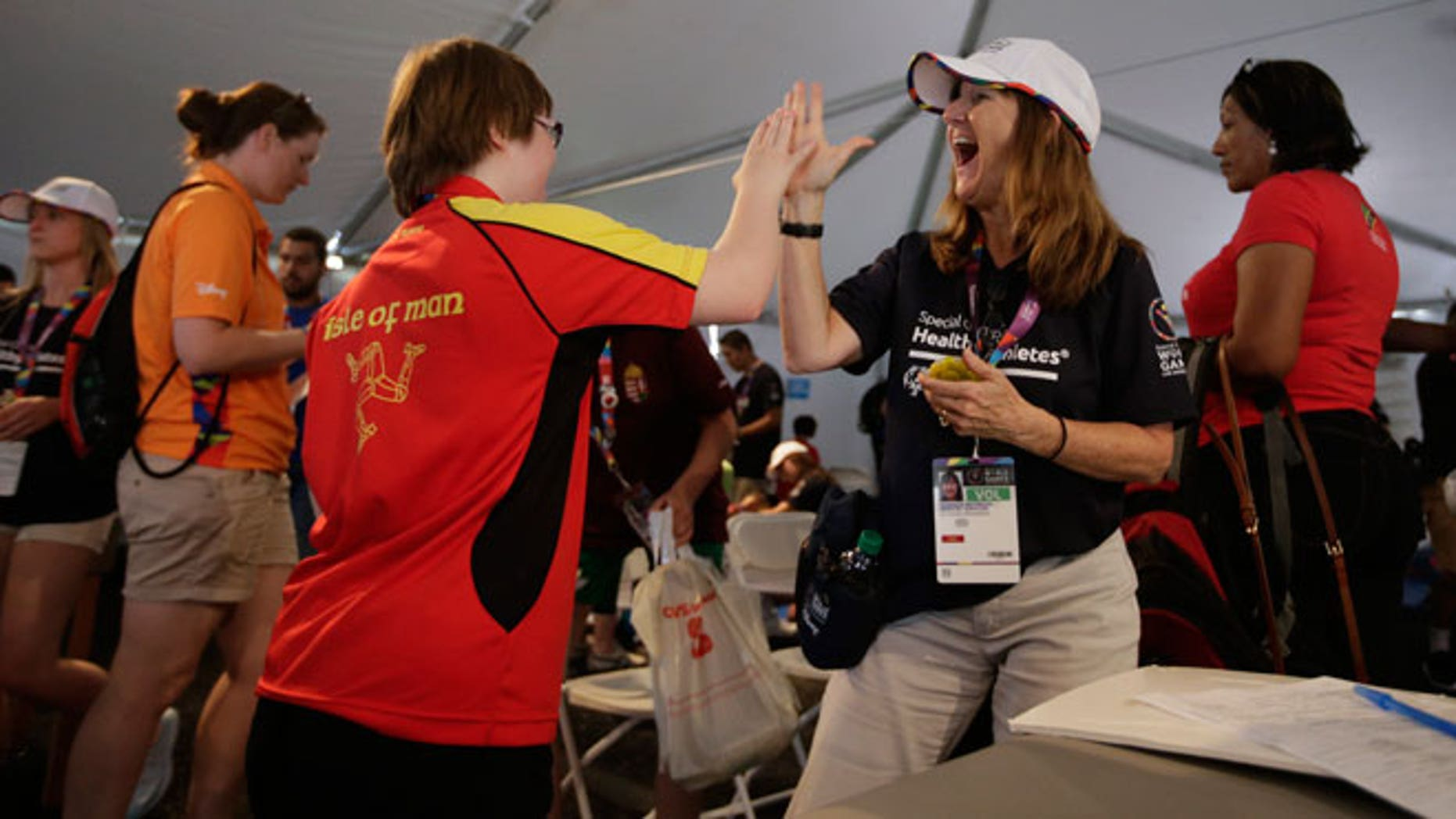 Volunteer Monique Peterson, right, high-fives an athlete from the Isle of Man after a balance test at the 2015 Special Olympics World Games, Tuesday, July 28, 2015, in Los Angeles. Organizers say many of these intellectually challenged athletes have never been examined by a doctor of any kind. Since it began in 1968, the Special Olympics' Healthy Athletes program has provided free medical services to more than 1.6 million people with intellectual disabilities.
