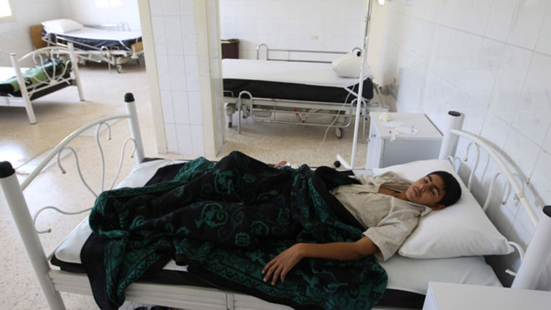 A boy infected by typhoid from polluted water, lies at a hospital in al-Qouniya village in Idlib countryside, May 27, 2013.