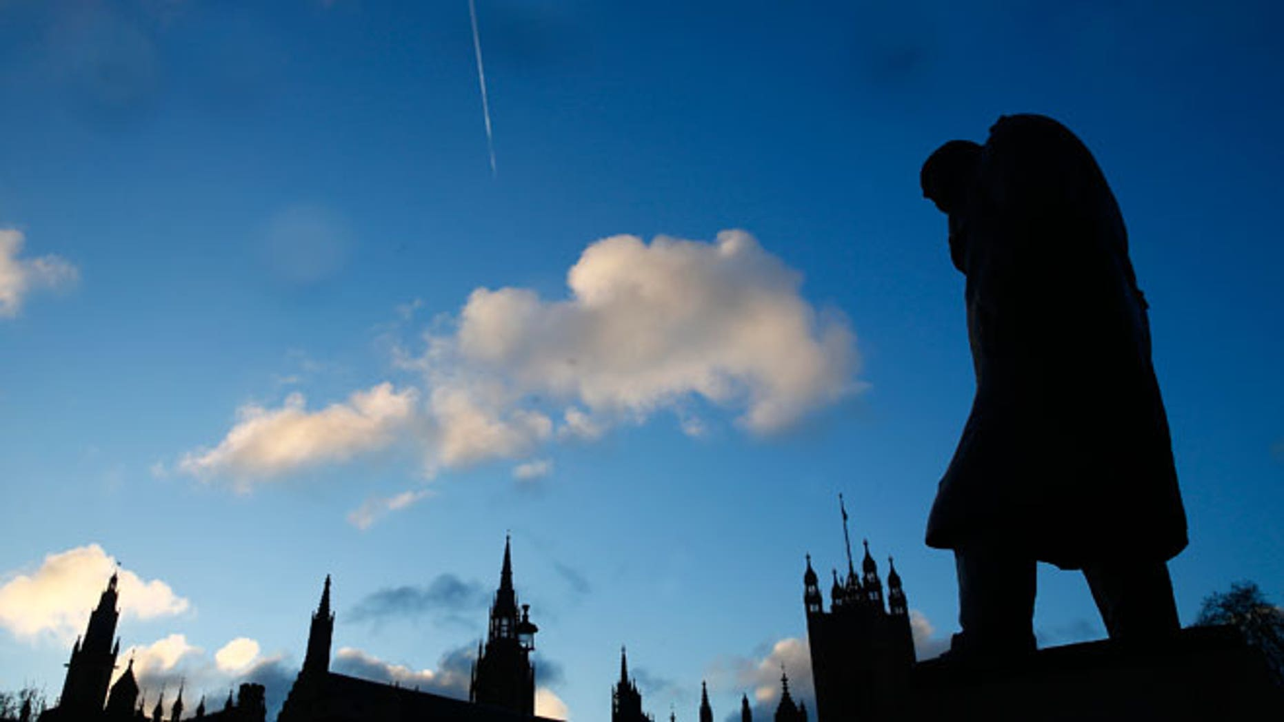 The statue of Britain's former Prime Minister Winston Churchill is silhouetted in front of the Houses of Parliament in London, January 30, 2015.