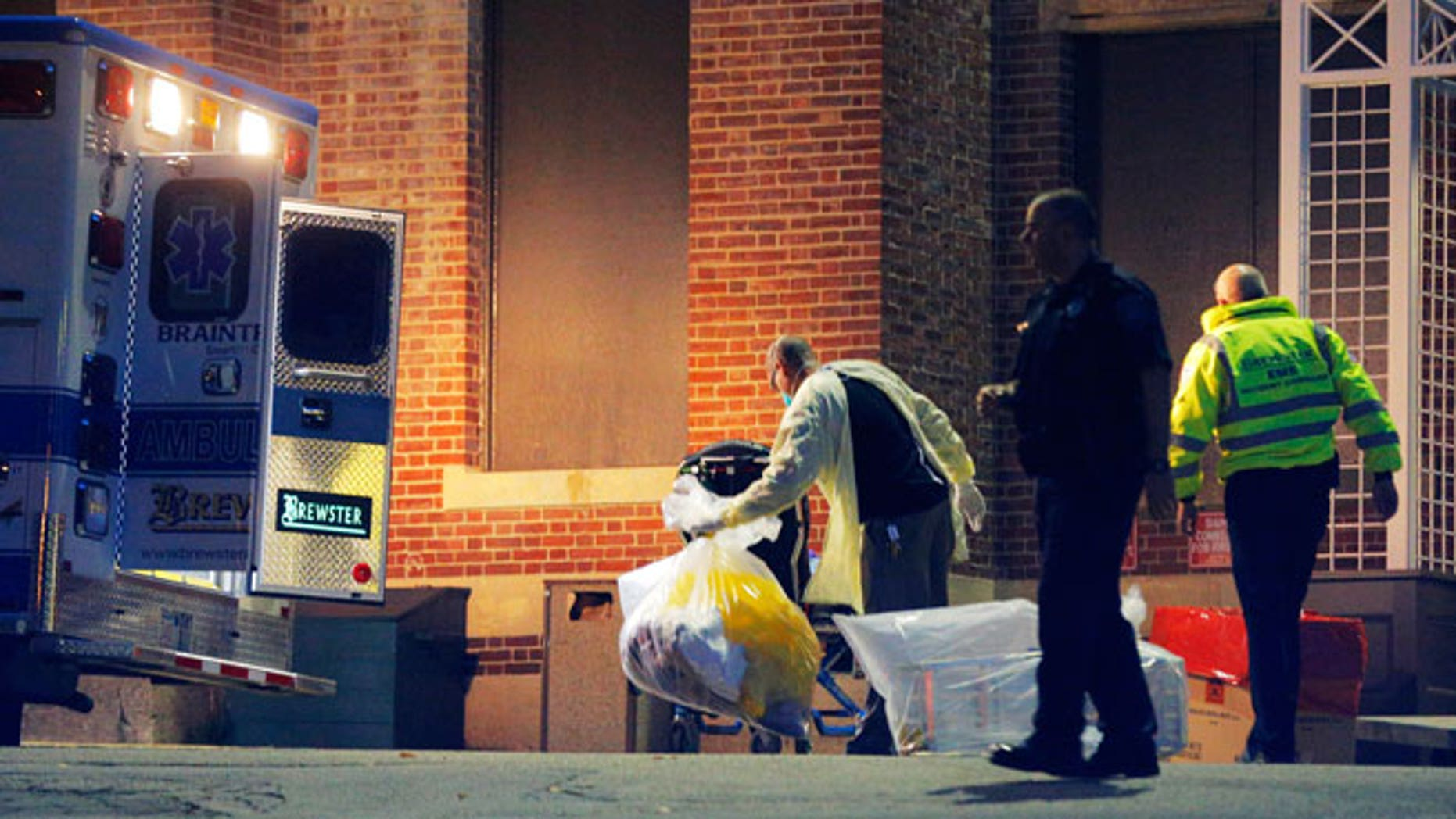 A man collects and bags items behind the ambulance used to transport a patient with possible Ebola symptoms to Beth Israel Deaconess Medical Center in Boston, Massachusetts October 12, 2014. A patient in Massachusetts who recently returned from Liberia and was displaying symptoms of Ebola was transferred from a medical clinic to a Boston hospital on Sunday, the hospital said. The patient has not been confirmed to have the deadly virus. REUTERS/Brian Snyder