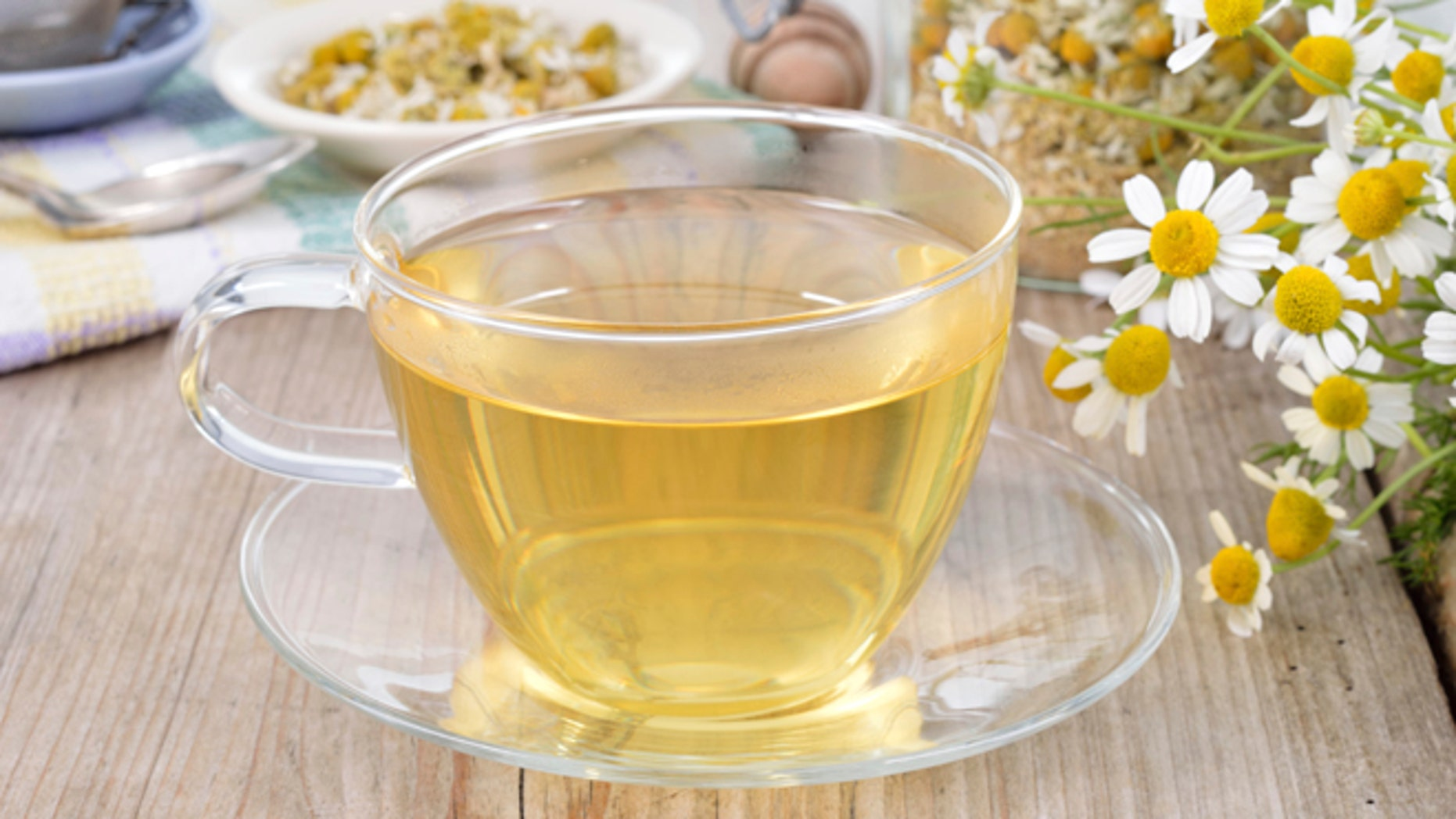 Cup of herbal chamomile tea on a wooden table. Chamomile tea in a transparent cup and camomile flowers on wooden table. Herbal tea for baby's stomach.