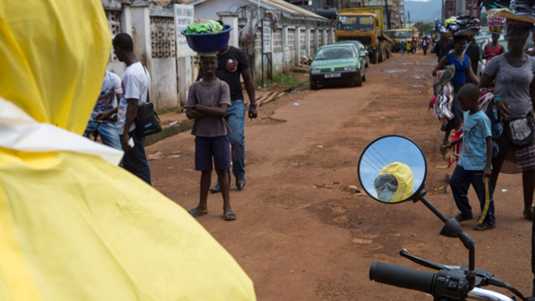 A health worker is reflected in a mirror as he prepares protective equipment near Rokupa Hospital, Freetown October 6, 2014.