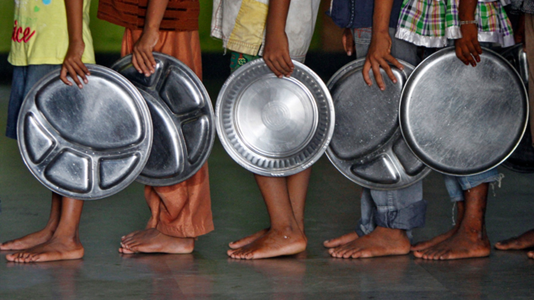Children holding plates wait in a queue to receive food at an orphanage run by a non-governmental organisation on World Hunger Day, in the southern Indian city of Chennai May 28, 2014. REUTERS/Babu (INDIA - Tags: SOCIETY) - RTR3R82F