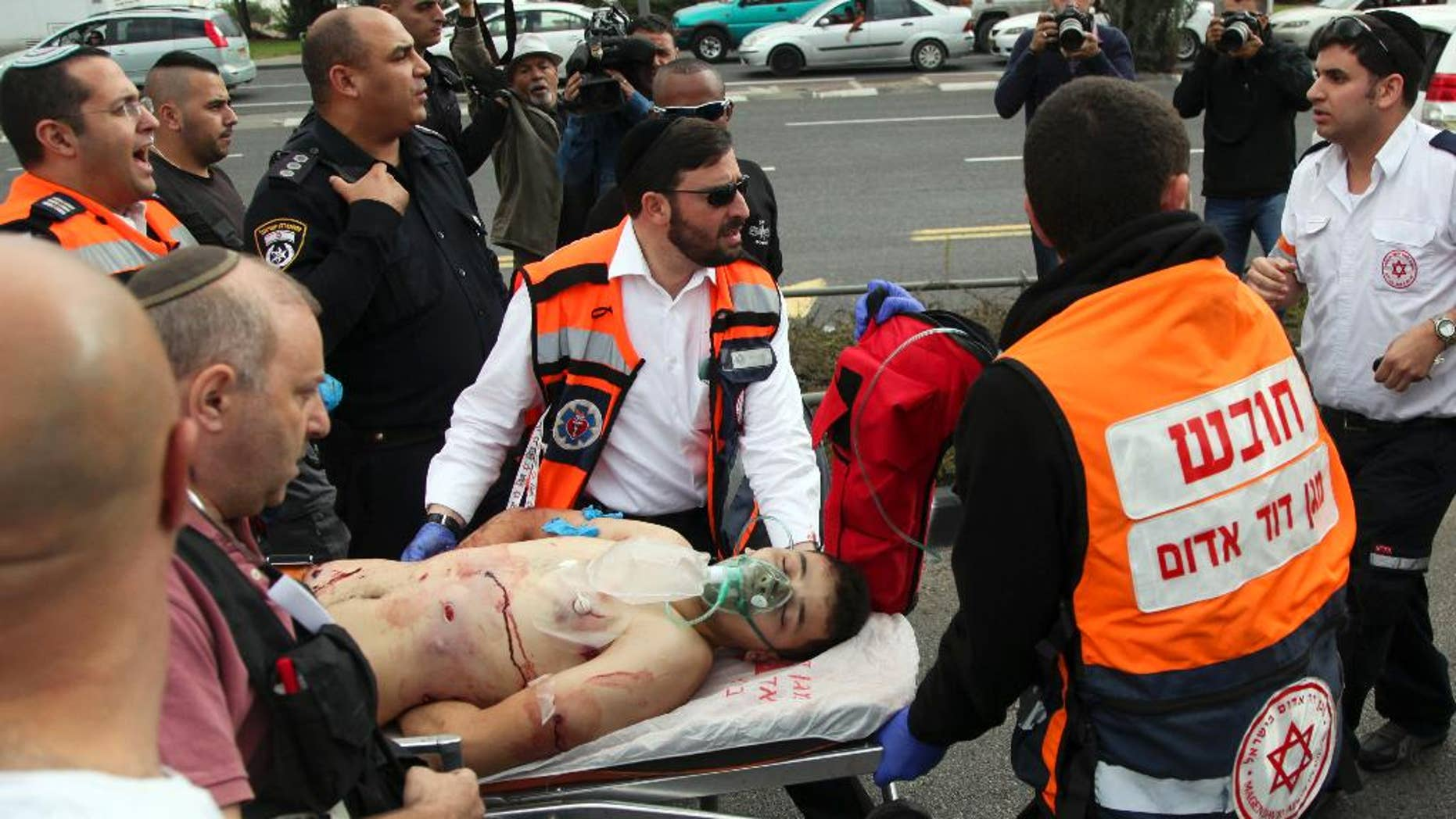 Paramedics evacuate a wounded Palestinian attacker in Jerusalem on Friday, Oct. 30, 2015. The Palestinian stabbed and seriously wounded a man at a station of Jerusalem's light rail Friday before he was shot and wounded by Israeli forces, police said. (AP Photo/Mahmoud Illean)