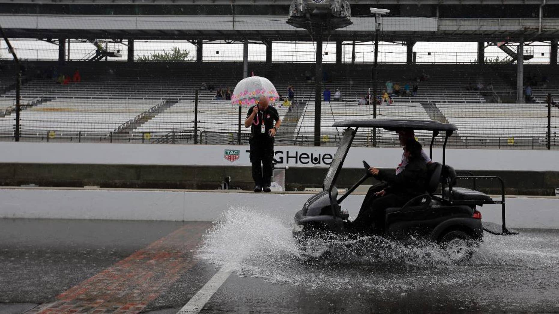 A cart splashes up water as its crosses the start/finish line as rain closed the track on the first day of qualifications for the Indianapolis 500 auto race at Indianapolis Motor Speedway in Indianapolis, Saturday, May 16, 2015.  (AP Photo/Darron Cummings)