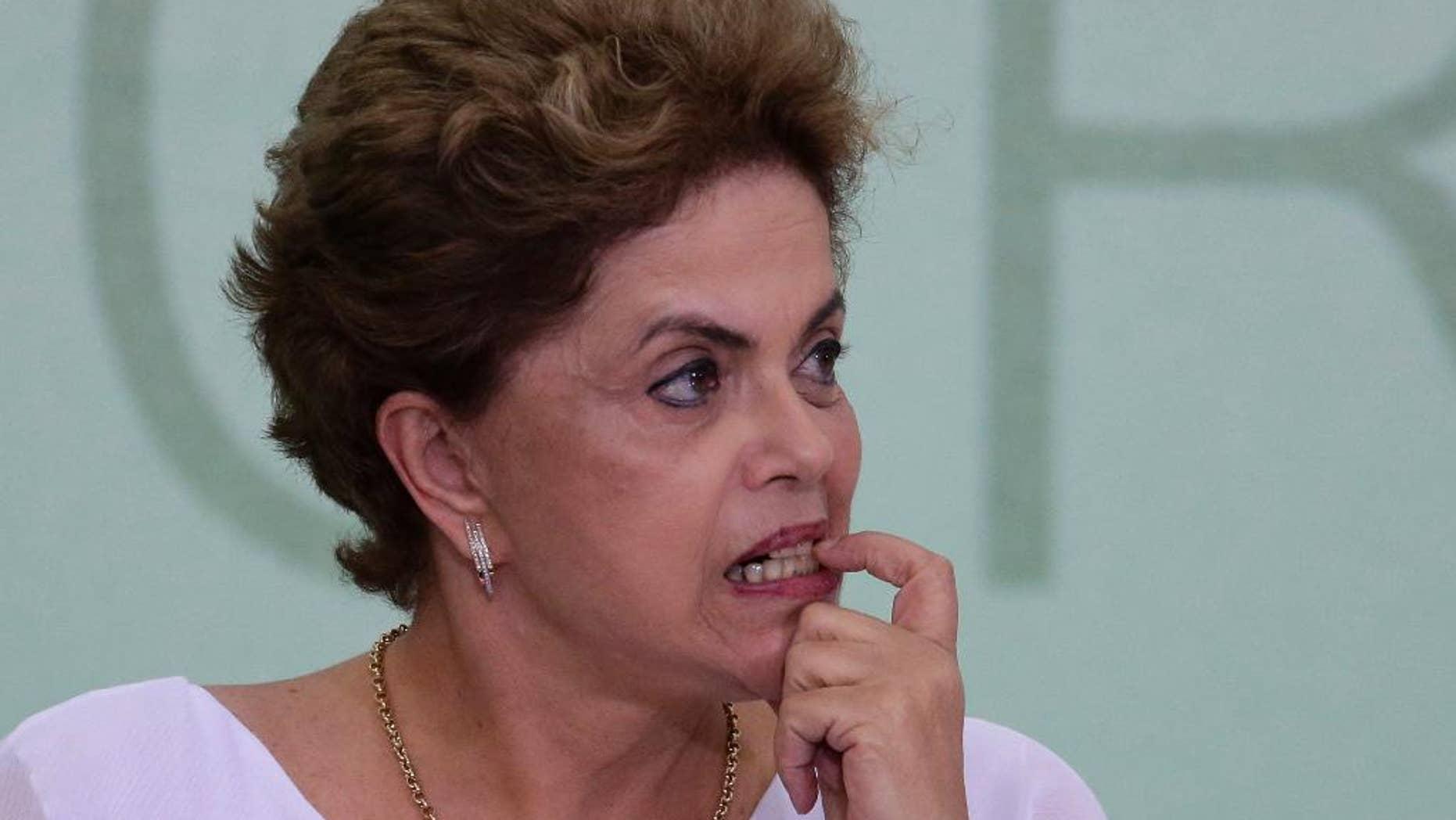 En esta imagen del viernes 1 de abril de 2016, la presidenta de Brasil, Dilma Rousseff, se muerde una uña durante una ceremonia de firma de acuerdos de reforma de tierras en el palacio presidencial de Planalto, en Brasilia. Rousseff, que lucha contra la peor recesión que sufre brasil en décadas y un escándalo de corrupción que ha implicado a miembros de su círculo más cercano, afronta un proceso de juicio político por acusaciones de que incumplió las leyes fiscales. (AP Foto/Eraldo Peres)