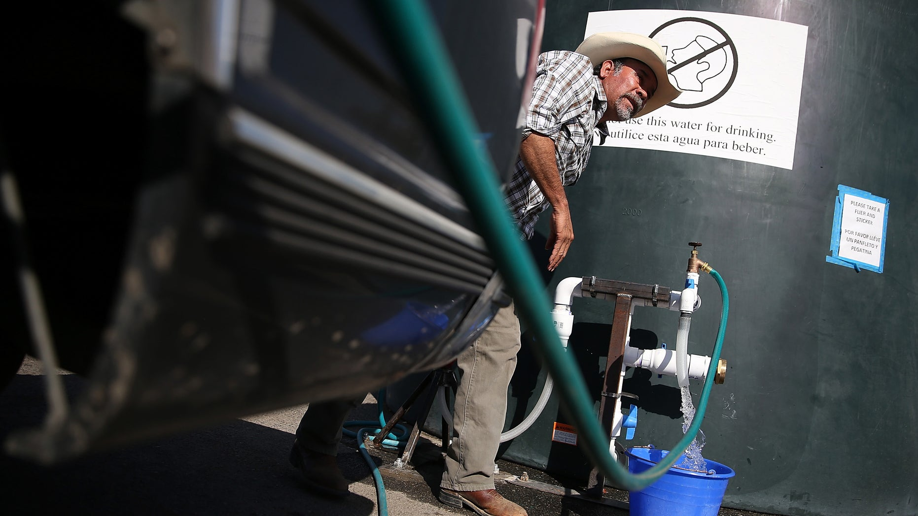 PORTERVILLE, CA - SEPTEMBER 04:  Mario Garcia fills buckets with non-potable water from a tank set up in front of the Doyle Colony Fire Station on September 4, 2014 in Porterville, California. More than 300 homes in the California central valley city of Porterville have been without running water for weeks after their wells ran dry due to the severe drought. County officials and charitable organizations are providing drinking water and non-potable water for use in washing dishes and bathing.  (Photo by Justin Sullivan/Getty Images)