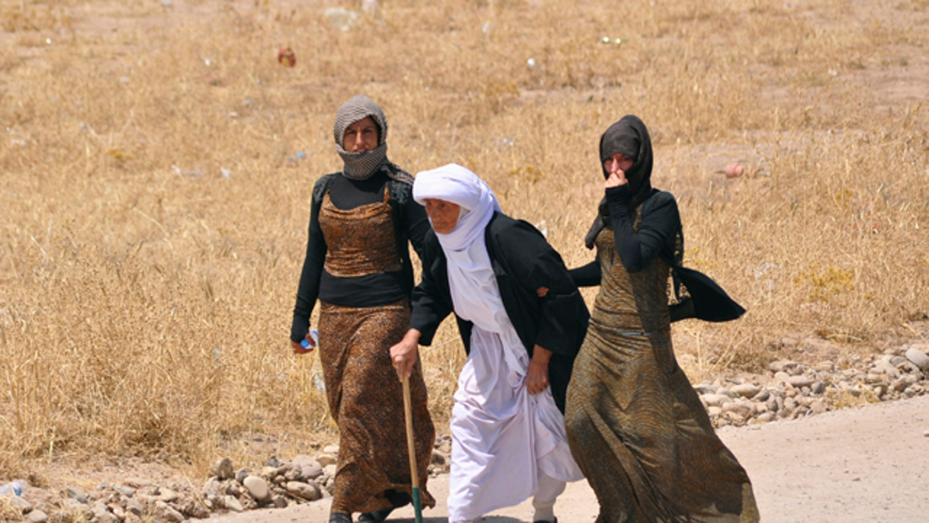 August 5, 2014: Displaced families from the minority Yazidi sect, fleeing the violence, walk on the outskirts of Sinjar, west of Mosul. (REUTERS)