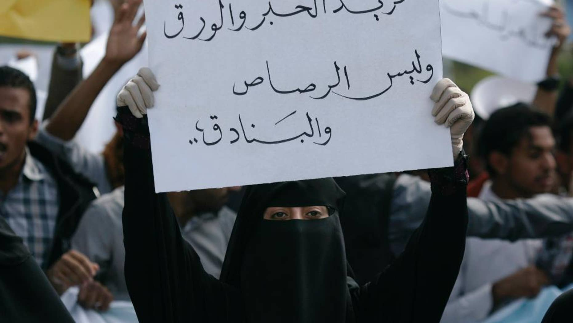"""A student holds a banner with Arabic that reads, """"we want ink and pens not bullets and rifles,"""" to protest against the Shiite insurgency during a rally at the University of Sanaa, Yemen, Tuesday, Nov. 25, 2014. (AP Photo/Hani Mohammed)"""