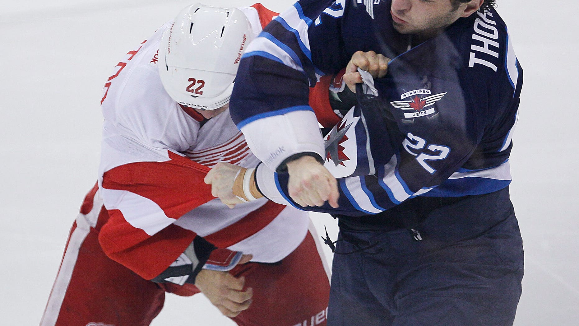 Detroit Red Wings' Jordin Tootoo (22) and Winnipeg Jets' Chris Thorburn (22) scrap during first period NHL action in Winnipeg on Monday, Nov. 4, 2013. (AP Photo/The Canadian Press, John Woods)