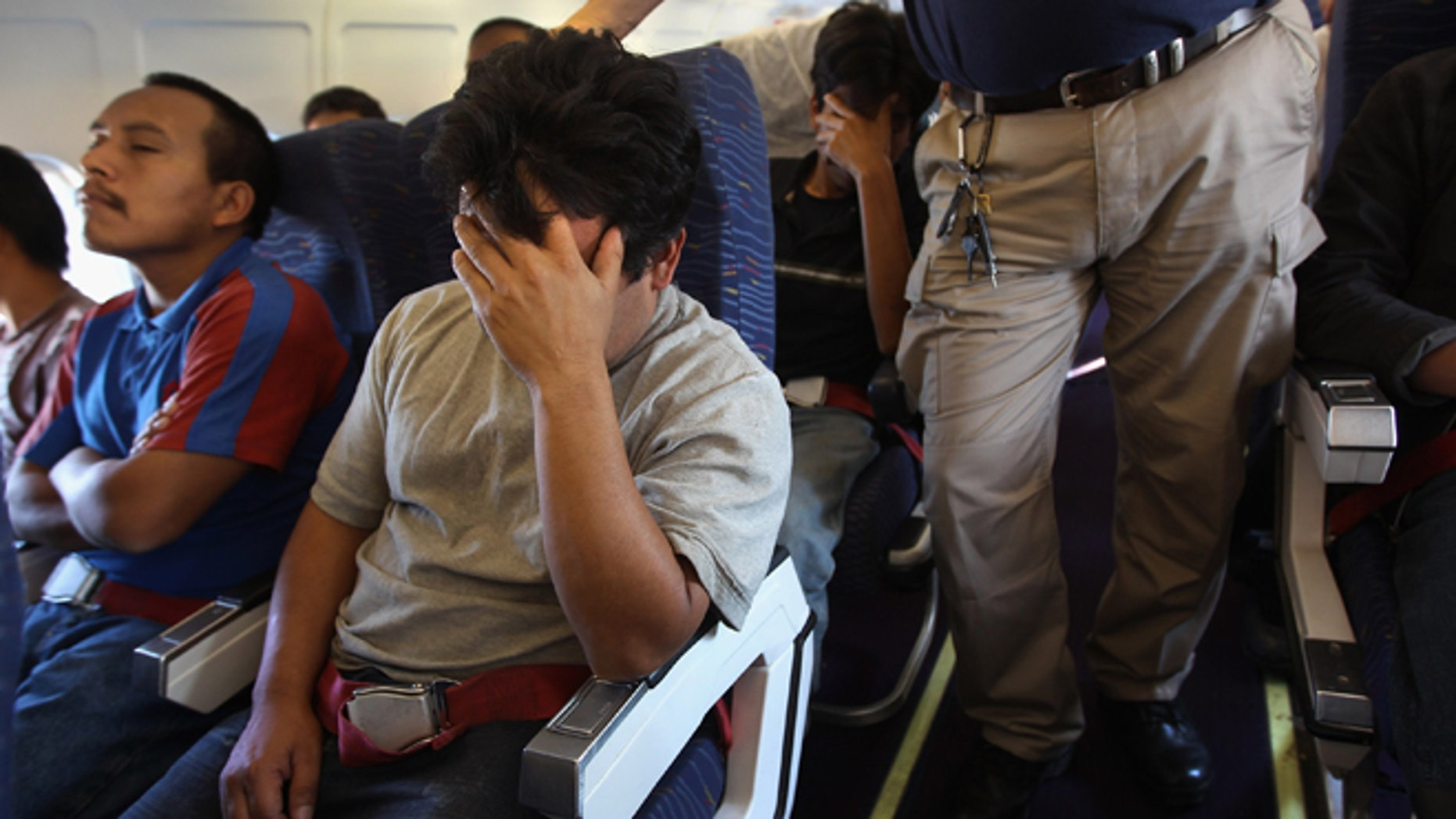 """IN FLIGHT - JUNE 24:  Undocumented Guatemalan immigrants are supervised by guards while on a deportation flight from Mesa, Arizona on June 24, 2011 in flight to Guatemala City, Guatemala. The U.S. Immigration and Customs Enforcement agency, ICE, repatriates thousands of undocumented Guatemalans monthly, many of whom are caught in the controversial """"Secure Communities"""" data-sharing program which puts local police on the frontlines of national immigration enforcement. ICE recently announced a set of adjustments to the federal program after many local communities and some states, including New York, insisted on opting out, saying immigrants were being deported for minor offenses such as traffic violations. Guatemala ranks only second to Mexico in the number of illegal immigrants deported from the United States.  (Photo by John Moore/Getty Images)"""