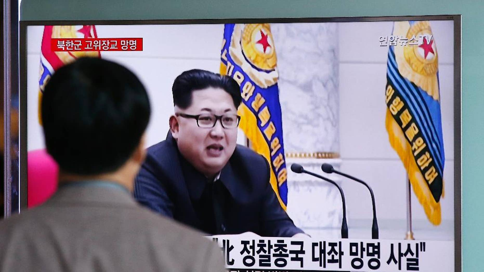 "A man watches a TV news program showing file footage of North Korean leader Kim Jong Un at Seoul Railway Station in Seoul, South Korea, Monday, April 11, 2016. A colonel from North Korea's military spy agency fled to South Korea last year in a rare senior-level defection, Seoul officials said Monday. The letters read ""True, A colonel from North Korean military's General Reconnaissance Bureau Asylum."" (AP Photo/Lee Jin-man)"