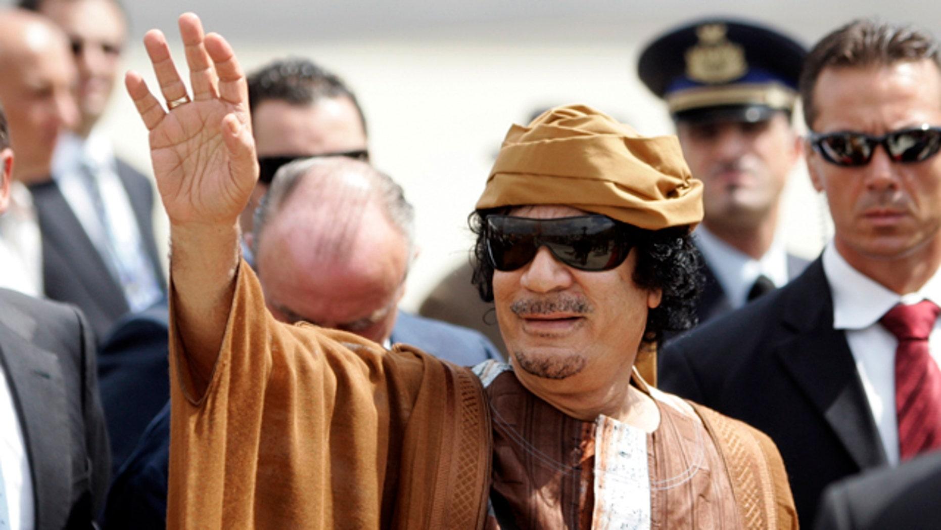 Aug. 29, 2010: Libyan leader Muammar Qaddafi gestures as he arrives at Ciampino airport, near Rome.