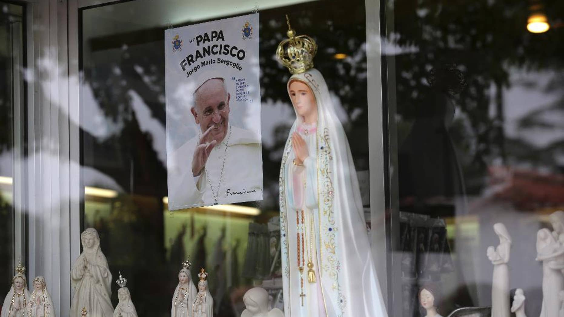 In this photo taken May 4 2017, a photo of Pope Francis, Francisco in Portuguese, is displayed on the window of a shop selling statues of Our Lady of Fatima in the village of Fatima, Portugal. Pope Francis is visiting the Fatima shrine on May 12 and 13 to canonize two Portuguese shepherd children who say they saw visions of the Virgin Mary 100-years ago. (AP Photo/Armando Franca)