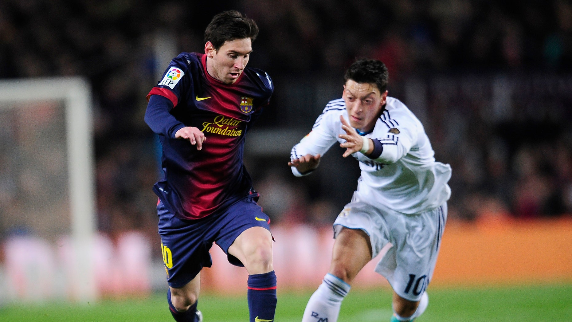 Barcelona's Lionel Messi from Argentina, left, and Real's Mesut Ozil from Germany challenge for the ball during a Copa del Rey soccer match between FC Barcelona and Real Madrid at the Camp Nou stadium in Barcelona, Spain, Tuesday, Feb. 26, 2013. (AP Photo/Manu Fernandez)