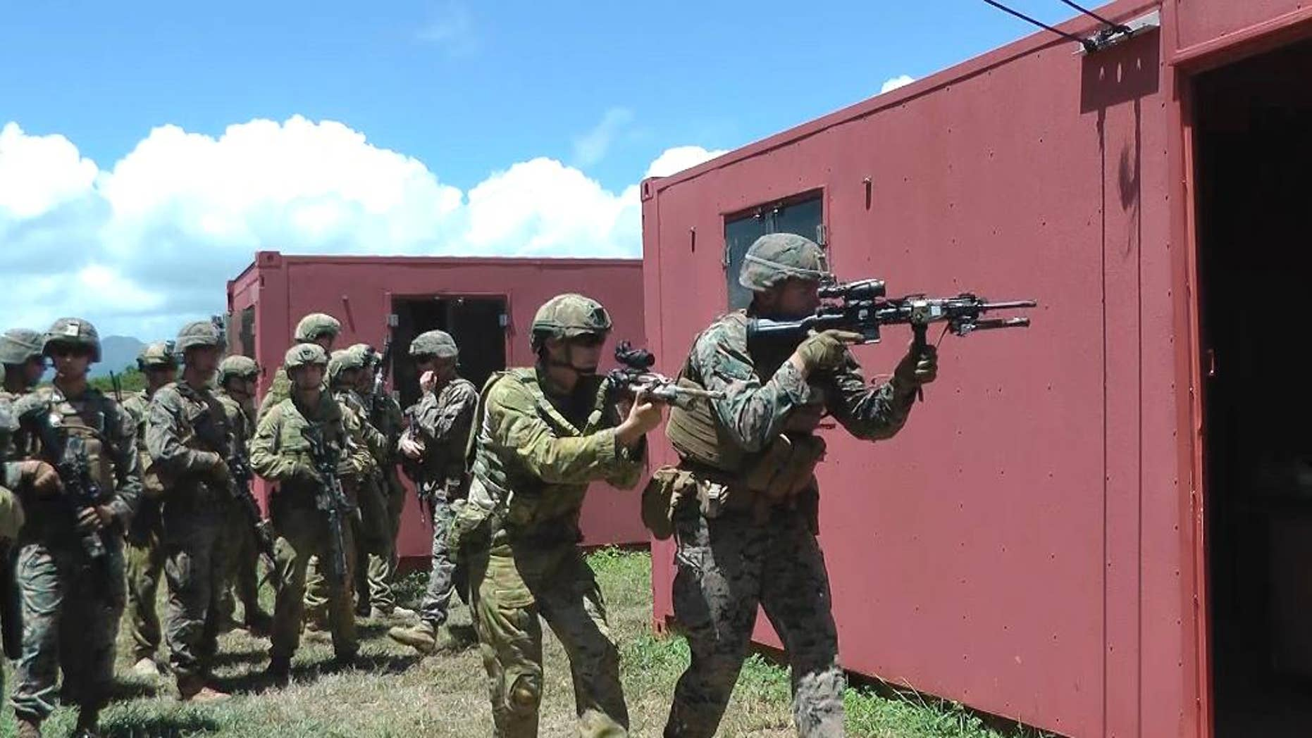 In this Thursday, July 7, 2016 photo, an Australian soldier, center left, and a U.S. Marine, right, get ready to raid a building at a mock urban combat training center in Kaneohe Bay, Hawaii. Australian soldiers are expected to lead a battalion of troops in the storming of a Hawaii beach during the world's largest maritime exercises this month, displaying the amphibious military skills they've been building up in recent years. (AP Photo/Audrey McAvoy)