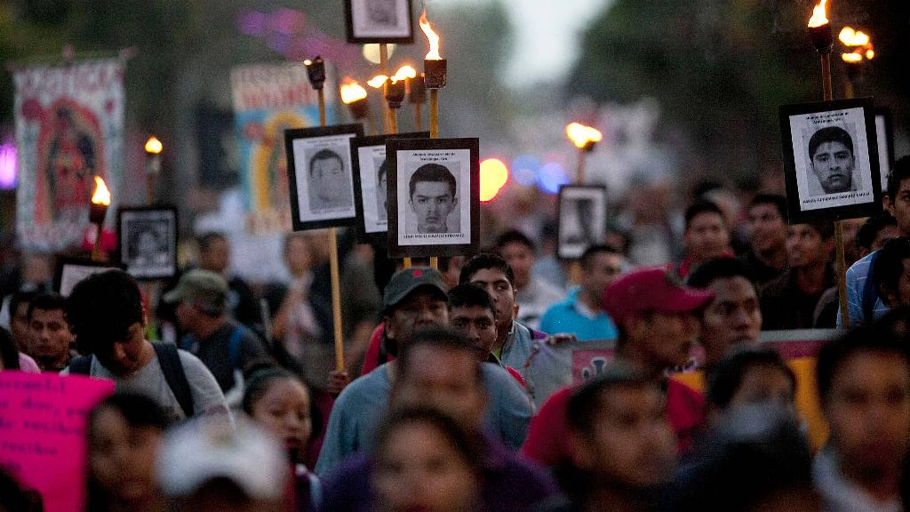 FILE - In this Dec. 26, 2015 file photo, relatives of the 43 missing students from the rural teachers college march holding pictures of their missing loved ones during a protest in Mexico City. Argentine forensic experts who have studied a dump in southern Mexico where government officials claim the bodies of 43 missing teachers' college students were burned say a new investigation of the site is incomplete and inconclusive. The Argentine Forensic Anthropology Team was called in shortly after the students from the Rural Normal School at Ayotzinapa disappeared in Iguala in Guerrero state on Sept. 26, 2014. (AP Photo/Marco Ugarte, File)