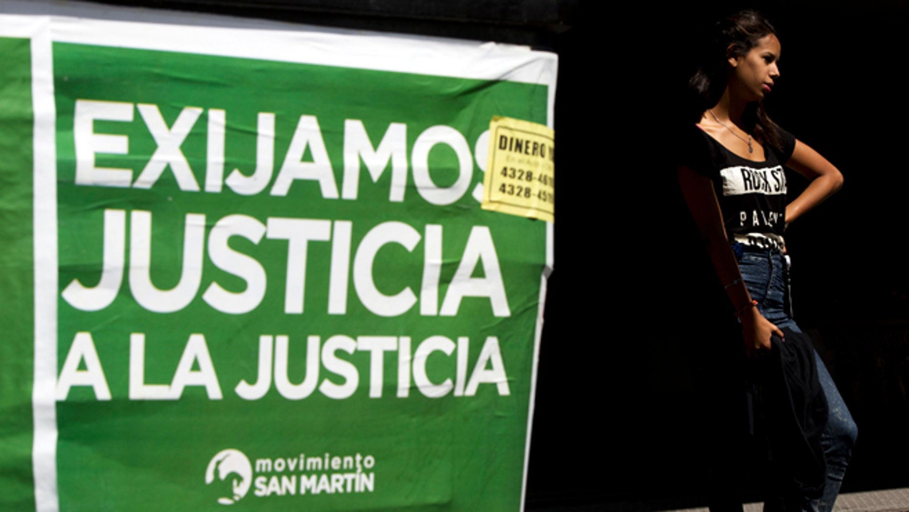 """A woman stands next to a poster that reads in Spanish """"Demand justice to justice"""", in reference to march organized by federal prosecutors demanding justice after the death of special prosecutor Alberto Nisman almost a month ago, in Buenos Aires, Argentina, Friday, Feb. 13, 2015. Nisman accused President Cristina Fernandez, Foreign Minister Hector Timerman and others in her administration of brokering the cover-up in the bombing of a Jewish community center in exchange for favorable deals on oil and other goods from Iran. Fernandez and Timerman have strongly denied the accusations, and Iran has repeatedly denied involvement in the bombing, which killed 85 people. (AP Photo/Rodrigo Abd)"""