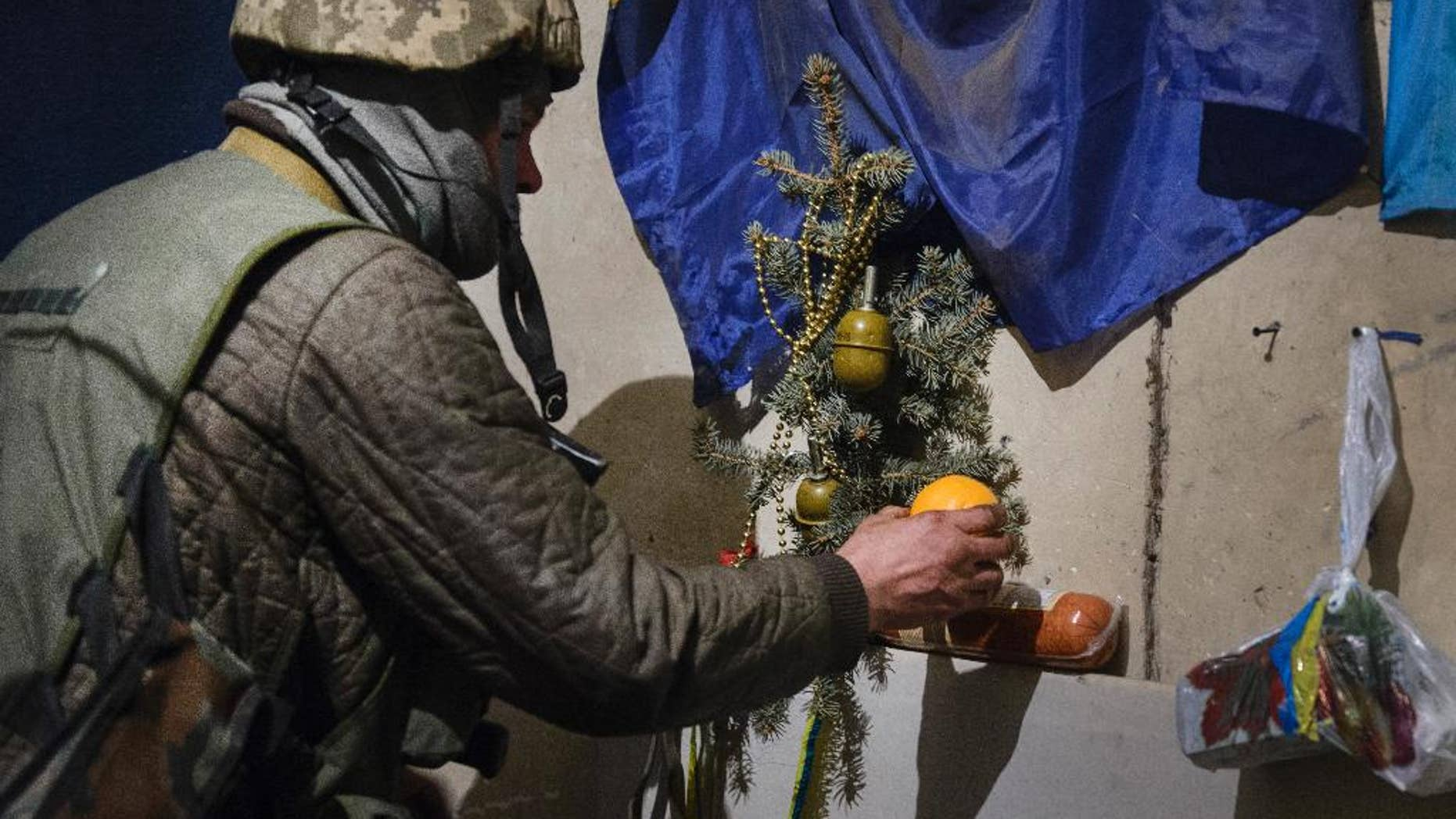 A Ukrainian soldier decorates a Christmas tree with grenades, a few hours before the New Year, in a shelter in the village of Peski near Donetsk, eastern Ukraine, Wednesday, Dec.31, 2014. (AP Photo/Olga Ivashchenko)