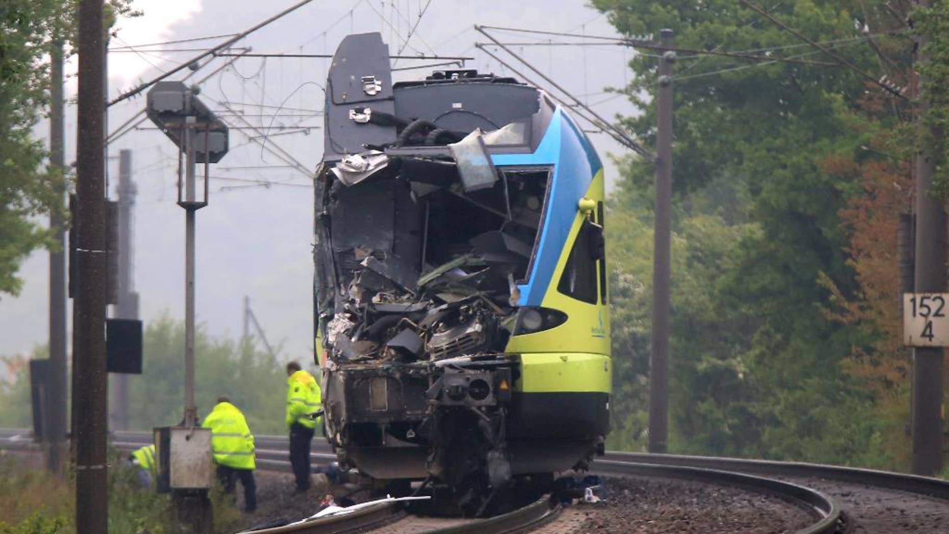 Workers are busy near the damaged train that hit a truck on a road crossing near Ibbenbueren, western Germany, Saturday, May 16, 2015. Police said two people have been killed and at least 20 others were injured in the accident. (Marcel Kusch/dpa via AP)