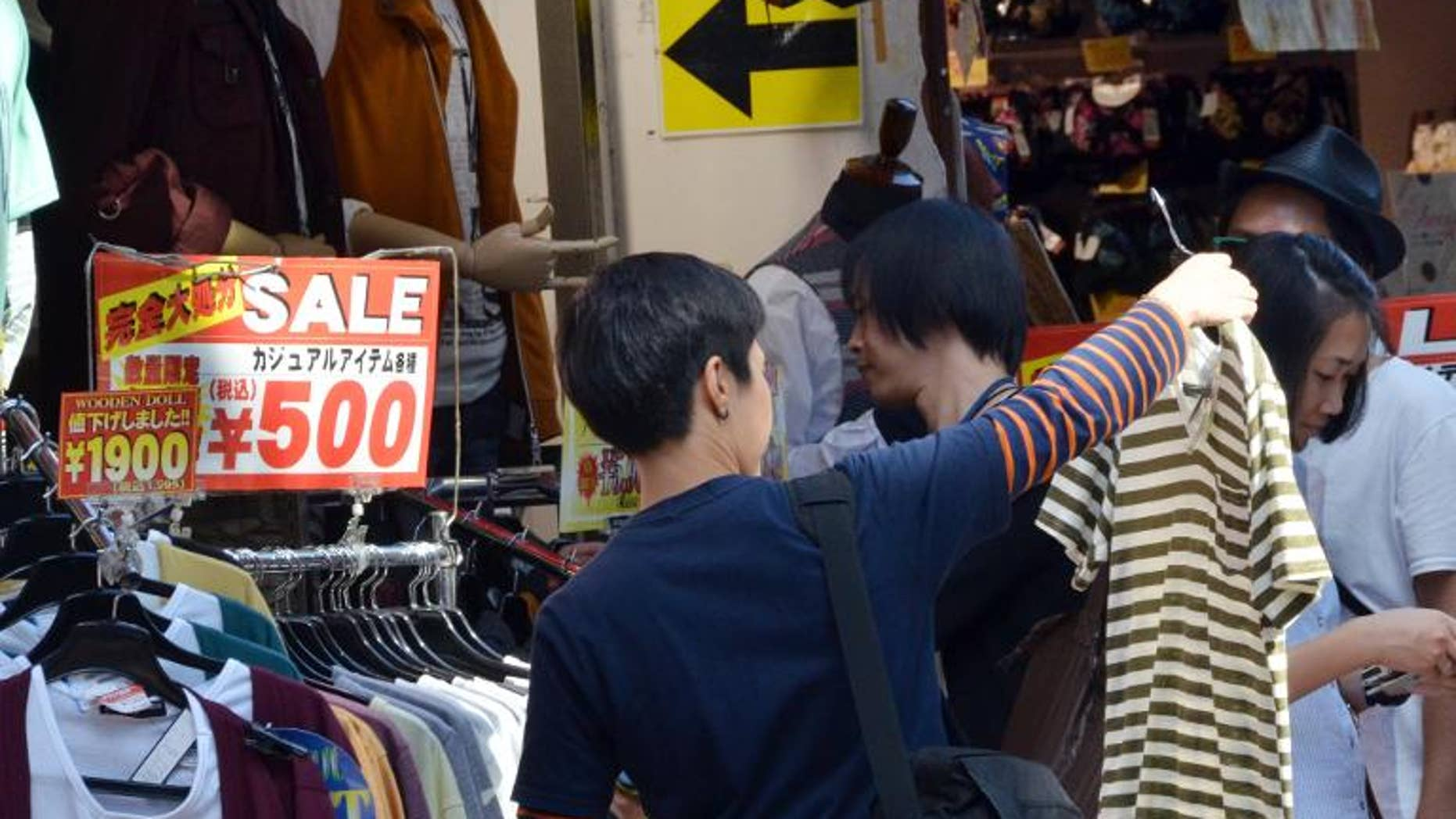 Shoppers look at clothing on sale outside a shop in Tokyo's Harajuku district, September 27, 2013