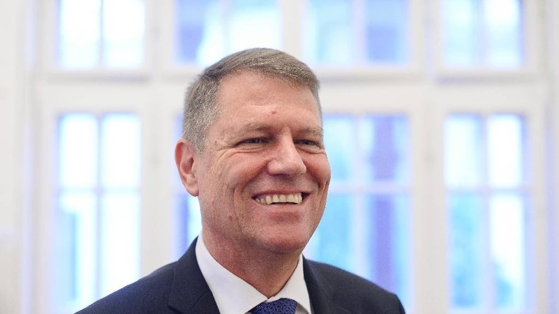 """Klaus Iohannis, leader of Romania's center-right Liberals and mayor of the Transylvanian city of Sibiu, smiles while posing for a portrait, shortly after giving an interview to the Associated Press, on the first morning after exit polls in the presidential elections runoff in Bucharest, Romania, Monday, Nov. 17, 2014. The ethnic German mayor who defeated Romania's Prime Minister Victor Ponta in a presidential runoff said his victory signaled """"a deep change"""" in Romania. (AP Photo/Octav Ganea, Mediafax) ROMANIA OUT"""