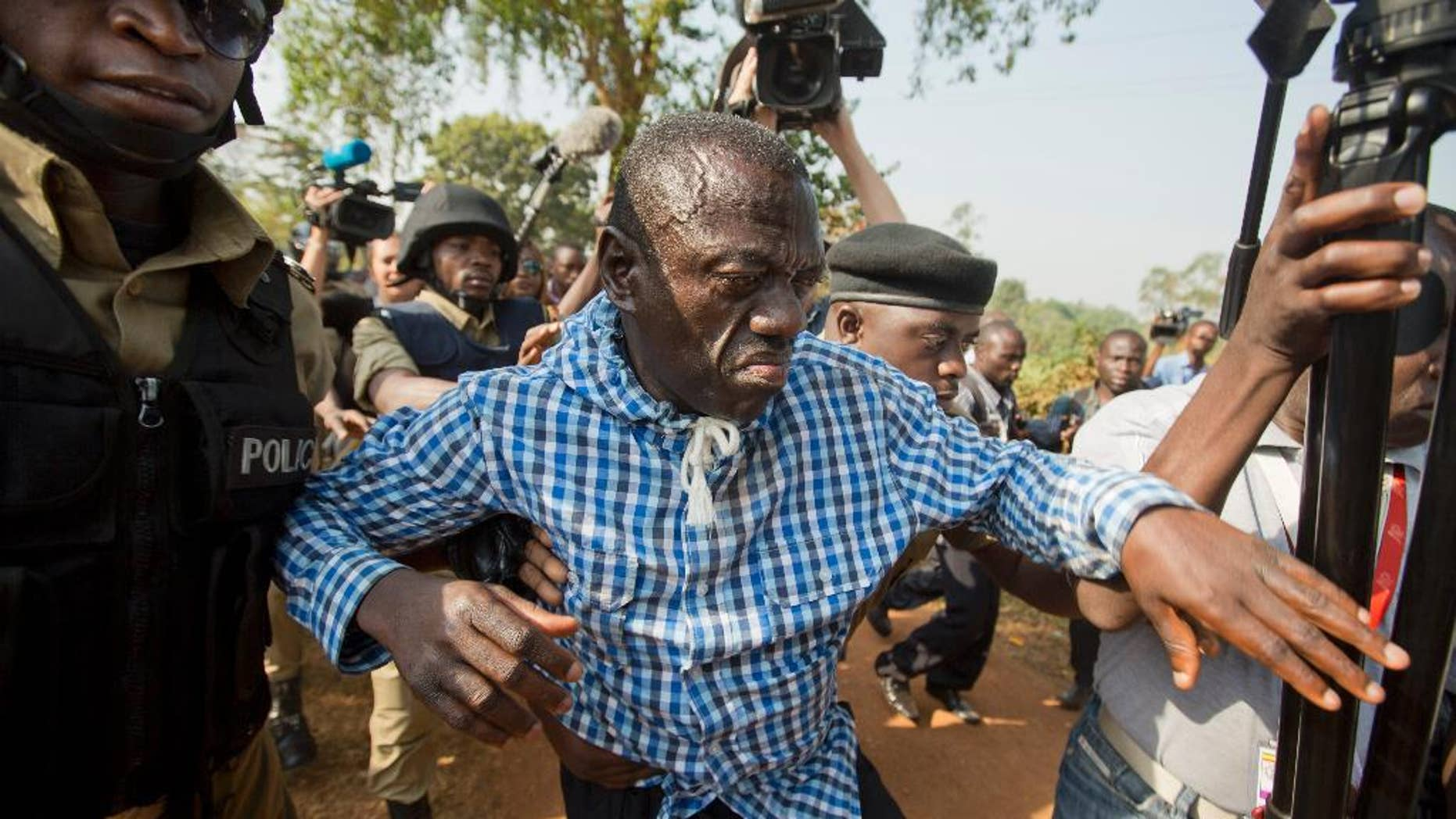 FILE - In this Monday, Feb. 22, 2016 file photo, Uganda's main opposition leader Kizza Besigye, center, is arrested by police and thrown into the back of a blacked-out police van, outside his home in Kasangati, Uganda. A spokesman for Uganda's judiciary said Saturday, May 14, 2016 that the main opposition leader Kizza Besigye has been flown to Moroto in the remote northeast of the country and charged with treason, a charge which attracts a maximum penalty of death upon conviction. (AP Photo/Ben Curtis, File)