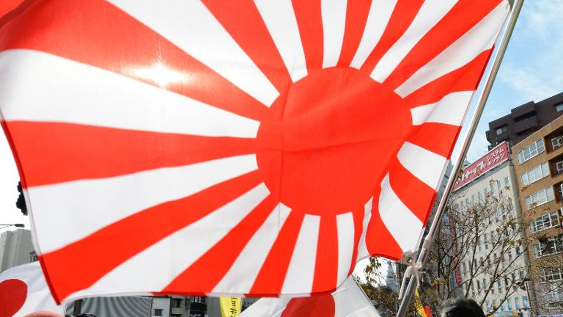 """Members of a nationalist group hold a """"Rising Sun"""" flag at a rally in Tokyo on February 22, 2013 over the disputed Takeshima/Dokdo islands"""