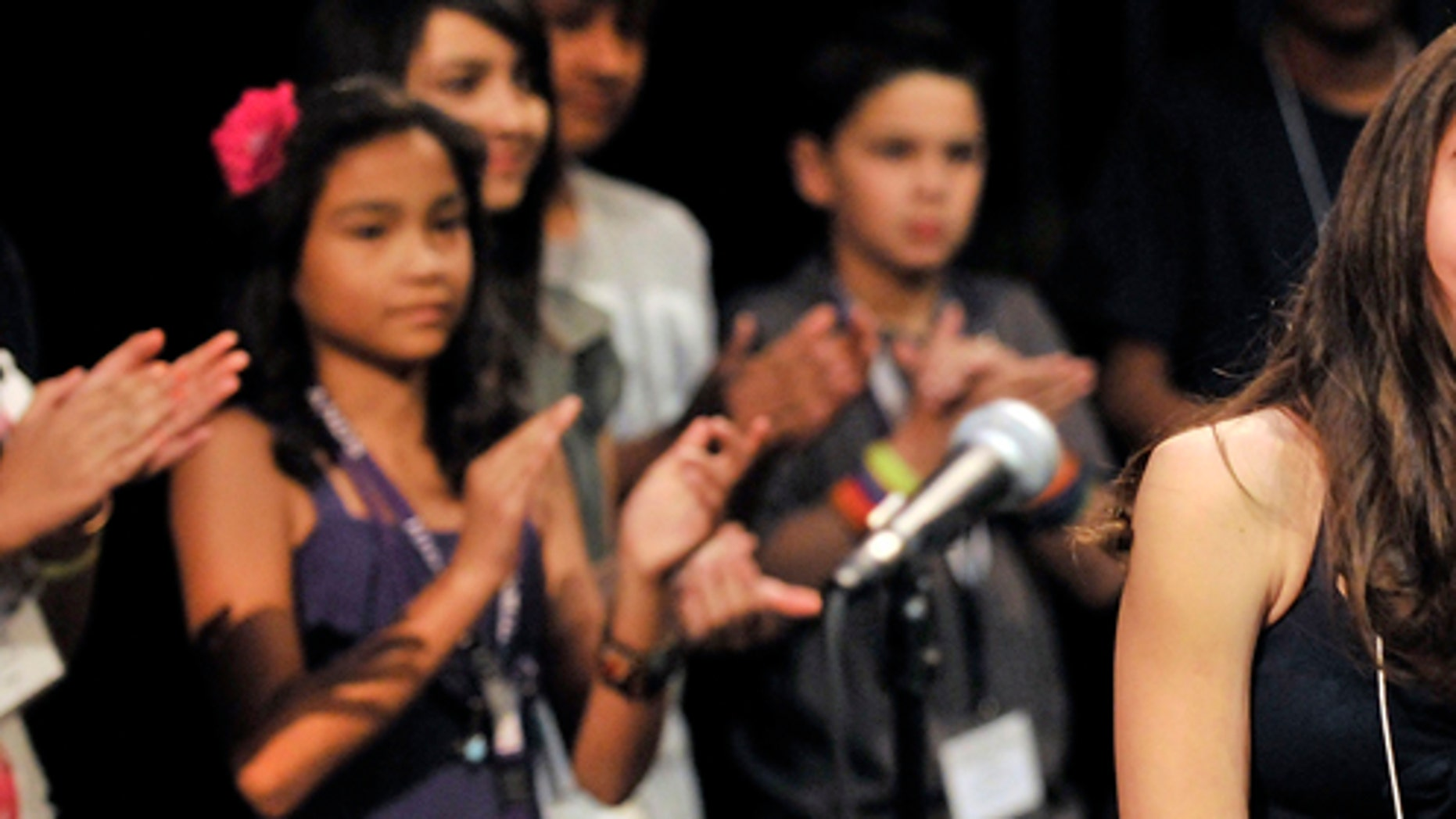Other contestants applaud Evelyn Juarez, right, a seventh grader from Santa Cruz, New Mexico, who won the First Annual SANTILLANA National Spanish Spelling Bee with the word bizantinismo at the National Hispanic Cultural Center in Albuquerque, NM on Saturday, July 9, 2011.  (AP Photo/Albuquerque Journal, Greg Sorber)
