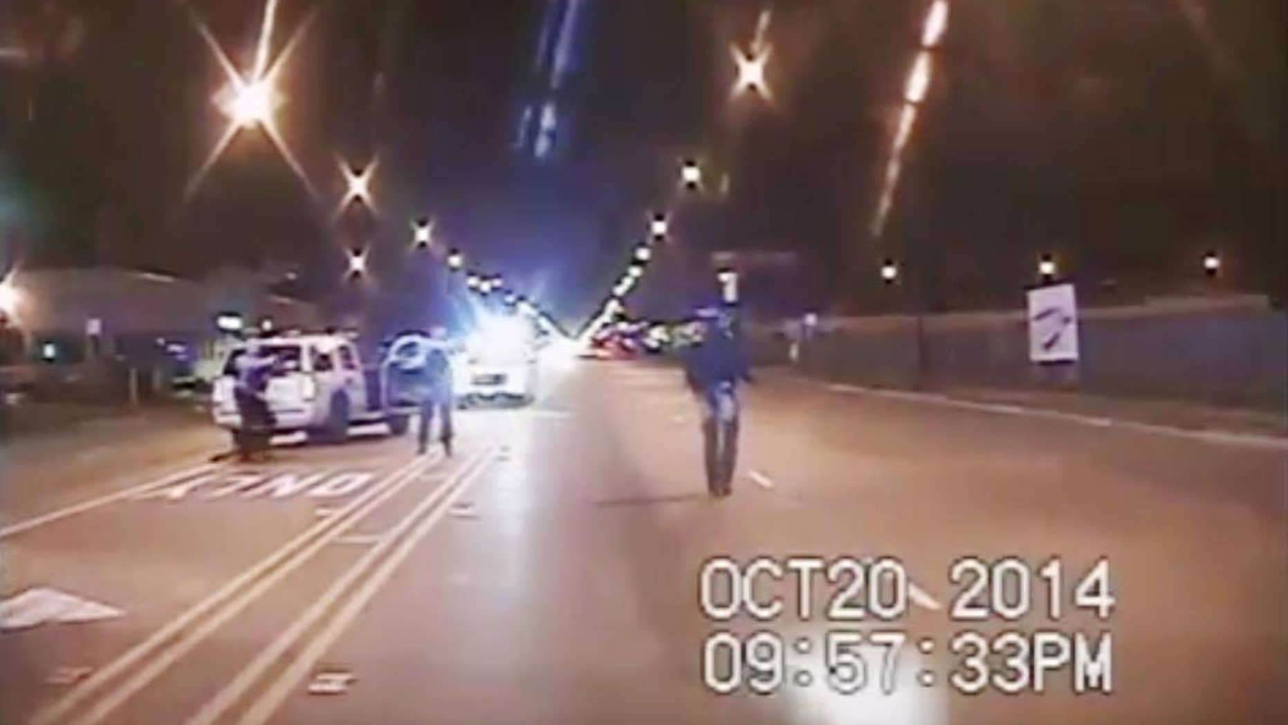 Oct. 20, 2014: In this image from dash-cam video provided by the Chicago Police Department, Laquan McDonald, right, walks down the street moments before being fatally shot by officer Jason Van Dyke sixteen times in Chicago.