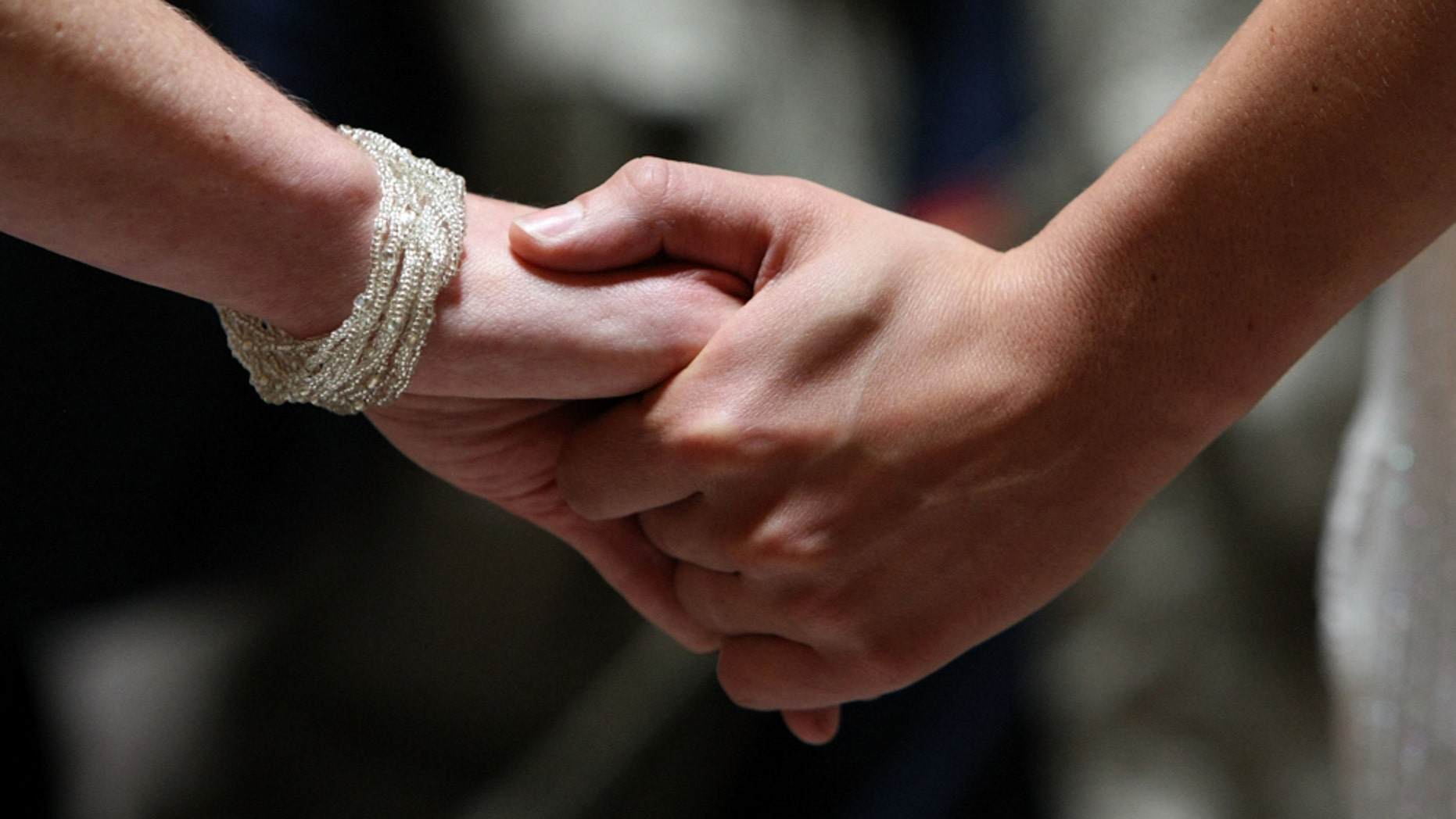 SAN FRANCISCO - JUNE 17:  Same-sex couple Amber Weiss and Sharon Papo hold hands as they get married at San Francisco City Hall June 17, 2008 in San Francisco, California. Same-sex couples throughout California are rushing to get married as counties begin issuing marriage license after a State Supreme Court ruling to allow same-sex marriage.  (Photo by Justin Sullivan/Getty Images)