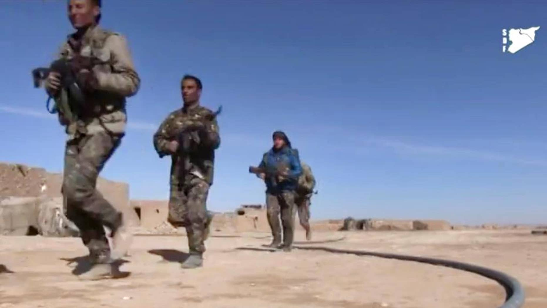 FILE - This frame grab from a video provided by the Syria Democratic Forces (SDF), shows fighters from the SDF running during fighting with Islamic State group militant, in Raqqa's eastern countryside, Syria, Monday, March 6, 2017. The main U.S.-backed force fighting the Islamic State group in Syria has enough fighters to capture the extremists' de facto capital of Raqqa north of the country at a time when U.S. troops are playing a bigger role on the ground in the battle to conquer the city, a spokeswoman for the force said Friday, March 10, 2017.  (Syria Democratic Forces, via AP)