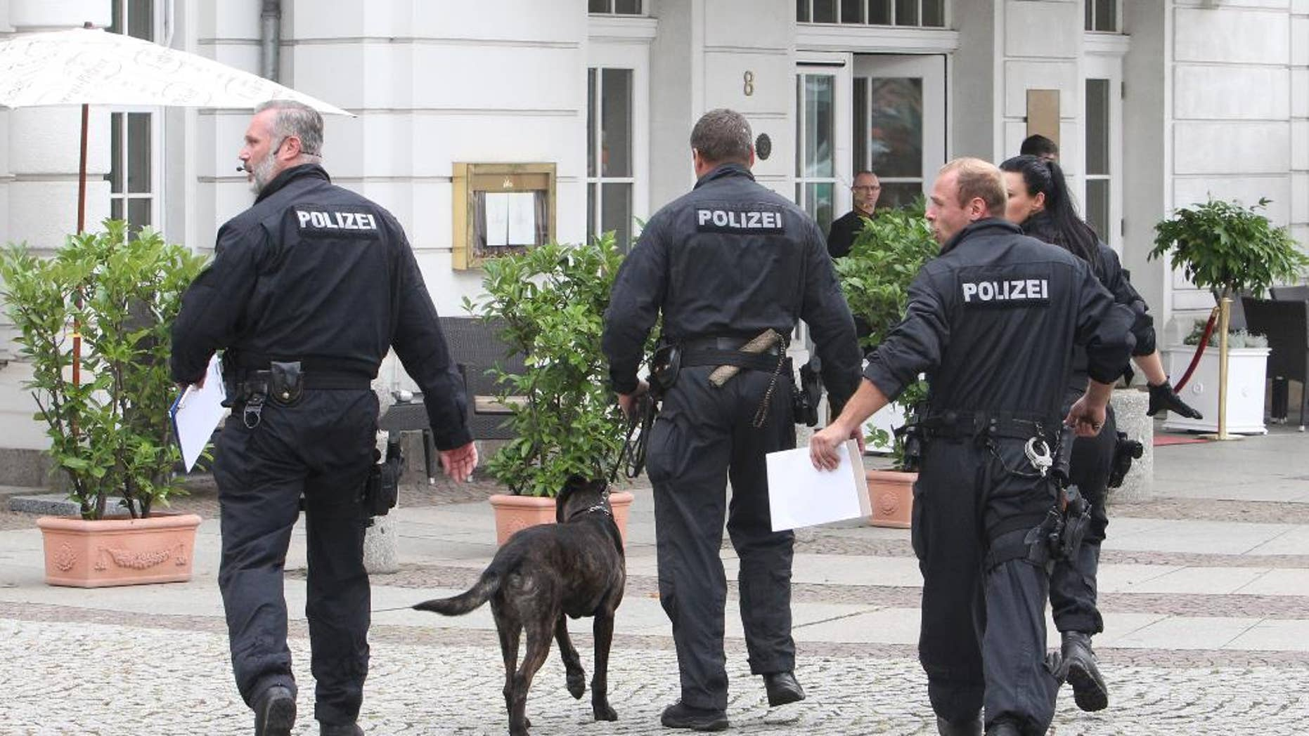 Police officers walk with a dog iinto the Hotel Fuerstenhof in Leipzig, Germany,Tuesday Sept. 6, 2016.  Police sealed off the hotel following a terror warning.  Police in the eastern city of Leipzig, Germany, are investigating an anonymous threat of an attack against a hotel and have established a heavy police presence in front of the building. Police spokesman Alexander Bertram said the upscale Fuerstenhof hotel received an anonymous phone call Tuesday. A search did not turn up anything suspicious. (Sebastian Willnow/dpa via AP)