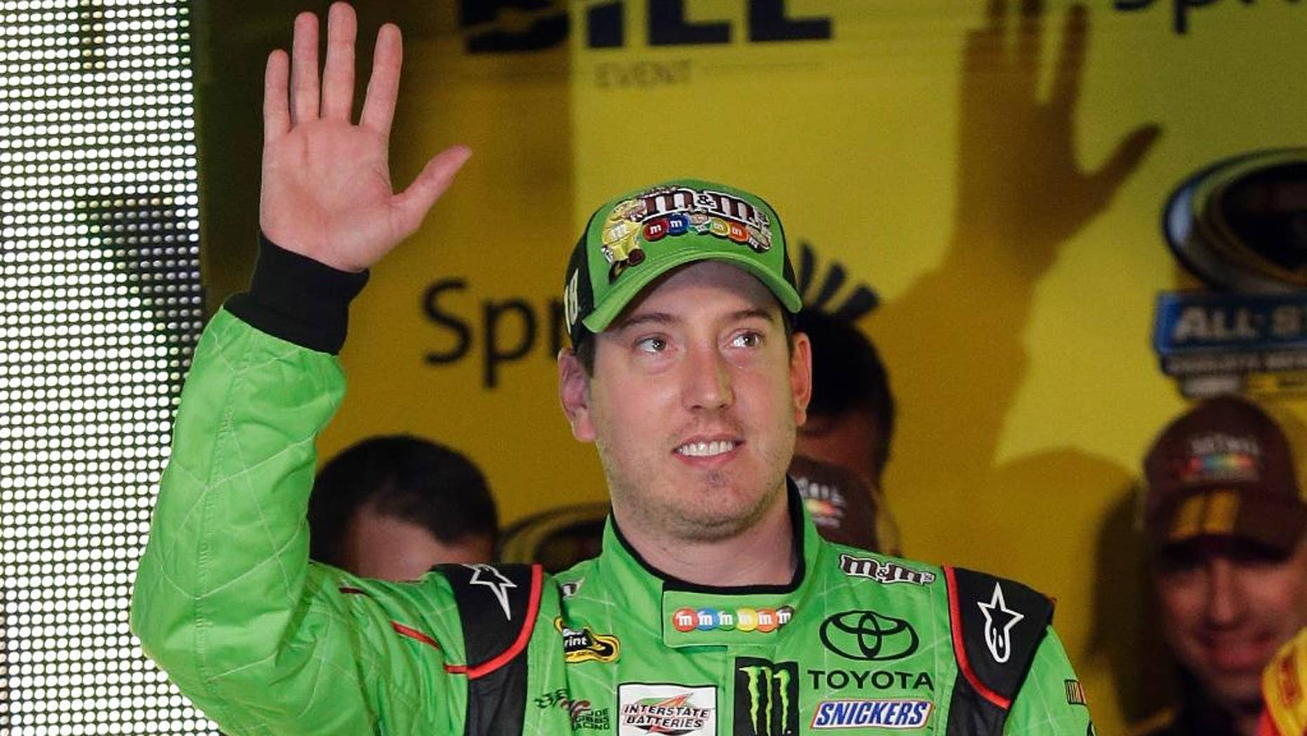 Kyle Busch waves during driver introductions for the NASCAR Sprint All-Star auto race at Charlotte Motor Speedway in Concord, N.C., Saturday, May 16, 2015. (AP Photo/Gerry Broome)