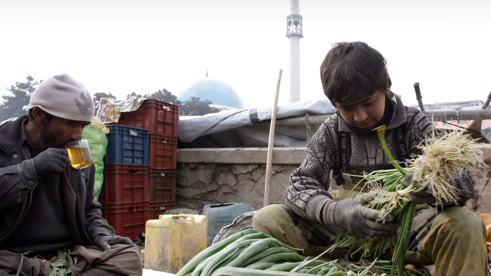 An Afghan vendor, right, sorts out vegetables as his father drinks tea during sorting of vegetable in Kabul, Afghanistan on Wednesday, Feb. 13, 2013. (AP Photo/Musadeq Sadeq)