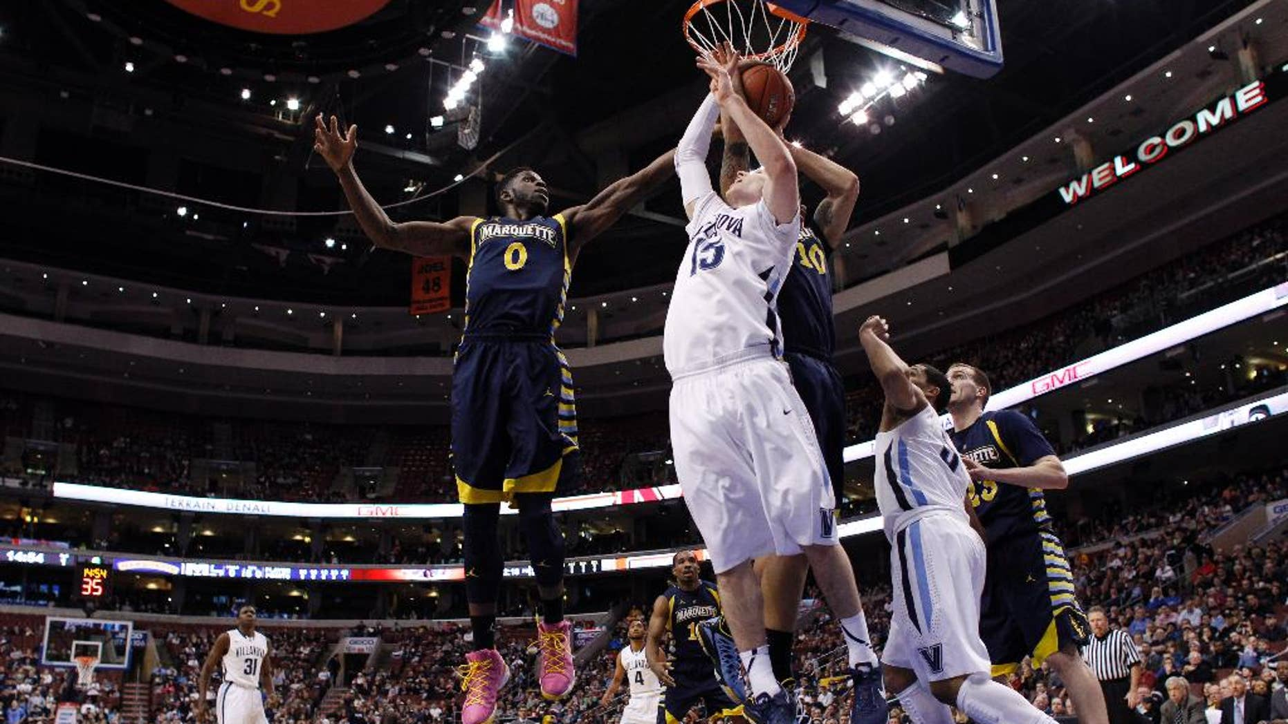 Villanova's Ryan Arcidiacono (15) battles for a rebound against Marquette's Jamil Wilson (0) and Juan Anderson (10) during the first half of an NCAA college basketball game on Sunday, March 2, 2014, in Philadelphia. (AP Photo/Matt Slocum)