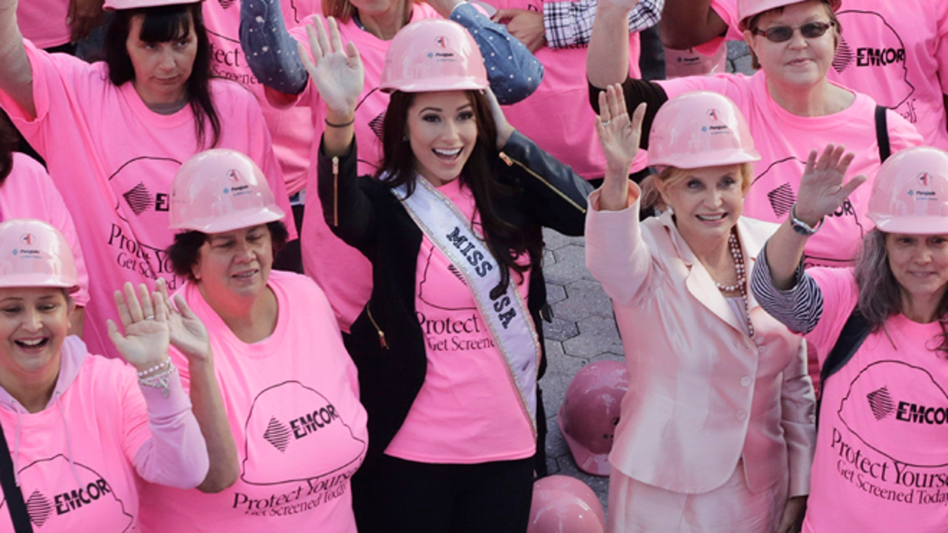 Nia Sanchez, center, Miss USA, joins hundreds of volunteers in pink hard hats and shirts to form a human pink ribbon in an event for Breast Cancer Awareness Month, Tuesday, Oct. 7, 2014 in New York. (AP Photo/Mark Lennihan)