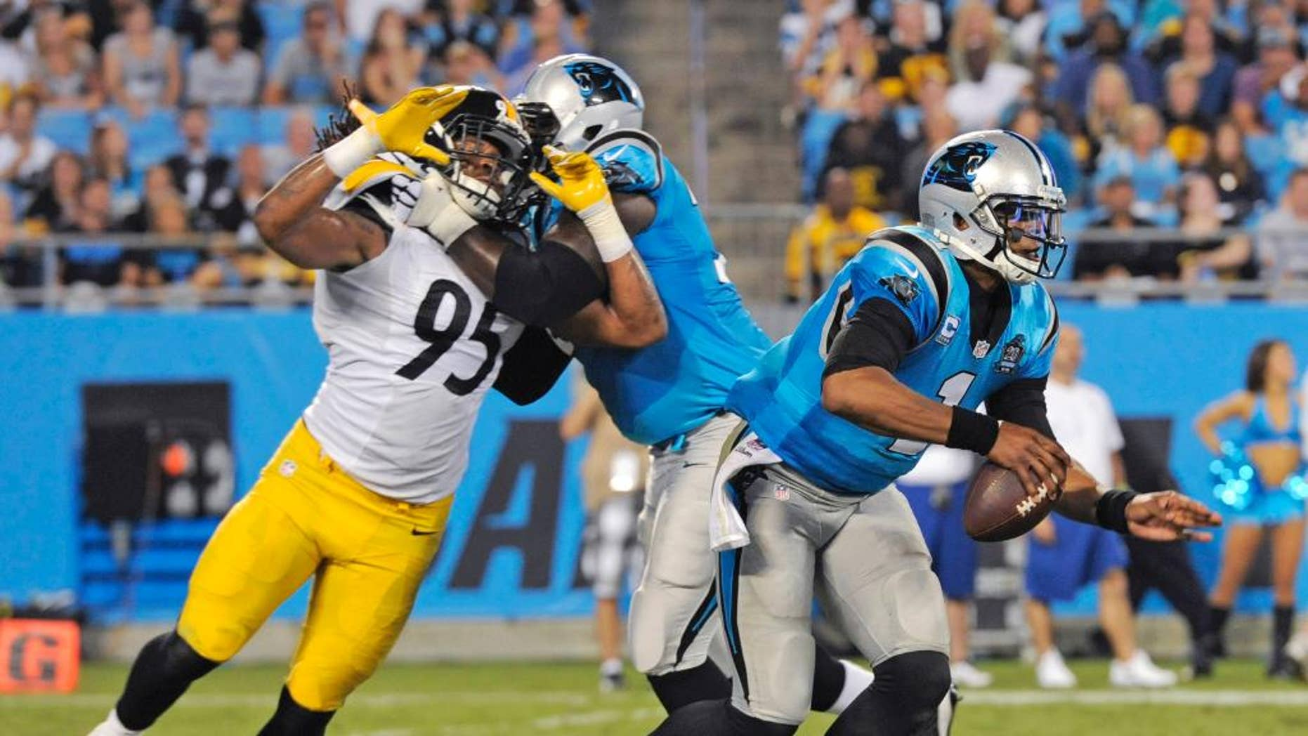Carolina Panthers' Cam Newton (1) scrambles past Pittsburgh Steelers' Jarvis Jones (95) during the second half of an NFL football game in Charlotte, N.C., Sunday, Sept. 21, 2014. (AP Photo/Mike McCarn)