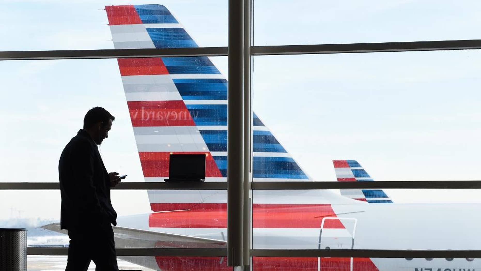 FILE - In this Jan. 25, 2016, file photo, a passenger talks on the phone as American Airlines jets sit parked at their gates at Washington's Ronald Reagan National Airport. American Airlines has agreed to pay $200 million for a stake in China Southern Airlines, the biggest of China's three major state-owned carriers, in a bid for a bigger share of the country's growing travel market. (AP Photo/Susan Walsh, File)