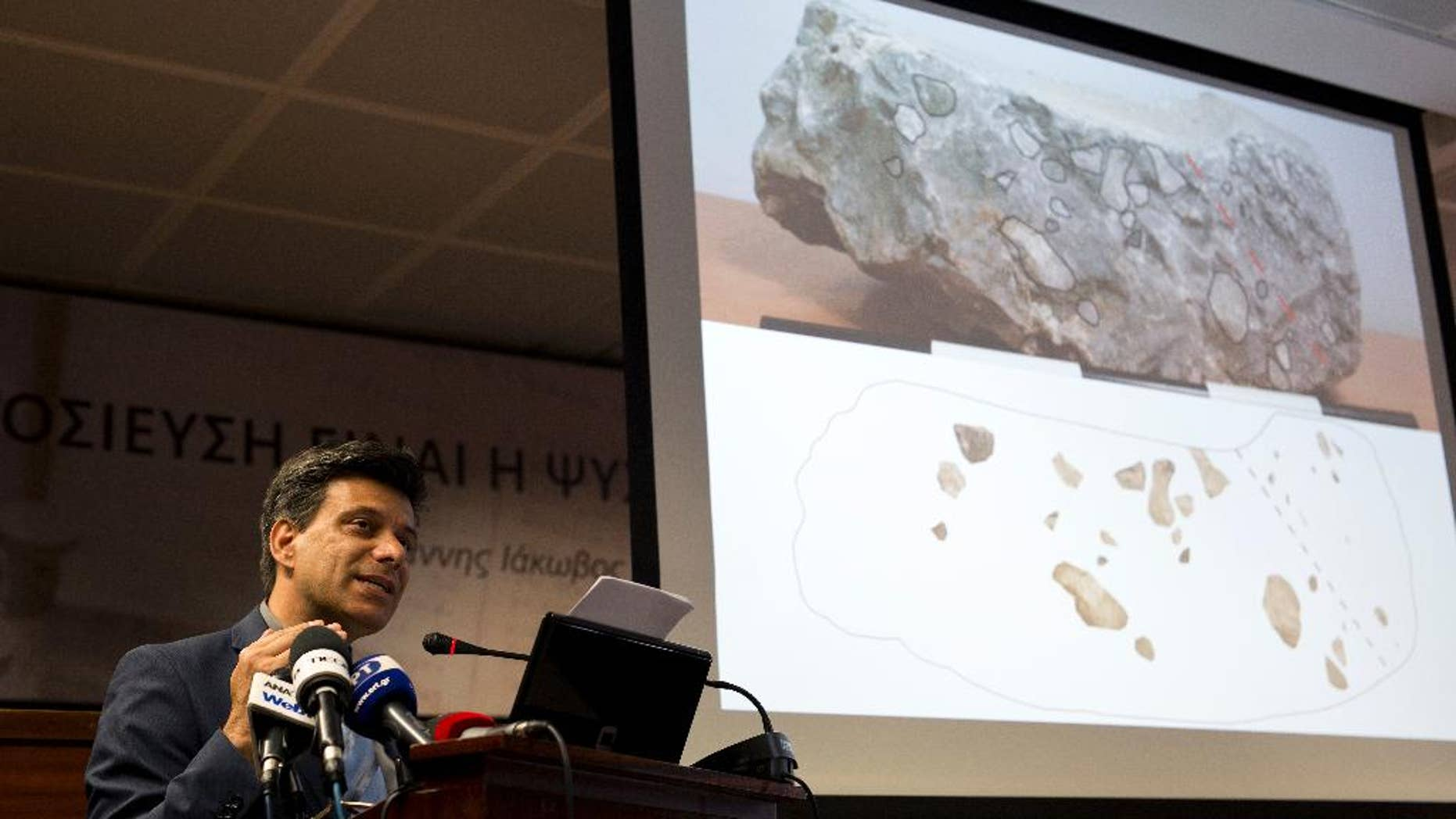 Greek archaeologist Christofilis Maggidis speaks as a photograph of a stone he believes belonged to the lost royal throne in the ancient palace of Mycenae, heart of the Mycenaean civilization, in southern Greece, during a press conference in Athens, on Tuesday, June 14, 2016. Maggidis says the worked stone, found by chance two years ago under the prehistoric citadel, is a chunk of the monolithic throne that was smashed when an earthquake sent part of the palace tumbling into a streambed below. (AP Photo/Petros Giannakouris