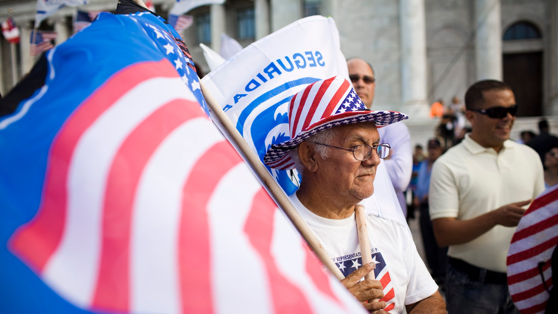 SAN JUAN, PUERTO RICO - MARCH 16:   Roberto Maldonado, 75, sells flags at a New Progressive Party rally where Republican presidential candidate, former Massachusetts Gov. Mitt Romney was campaigning on the North Side of the Capitol building March 16, 2012 in San Juan, Puerto Rico. Luis Fortuno, the island's governor and a Republican, has already expressed his support for the former governor for president. Romney's two-day campaign on the island is meant to win the 23 GOP delegates up for grabs on the U.S. territory. Romney's fiscal views are likely to resonate with the island's large private sector. (Photo by Christopher Gregory/Getty Images)
