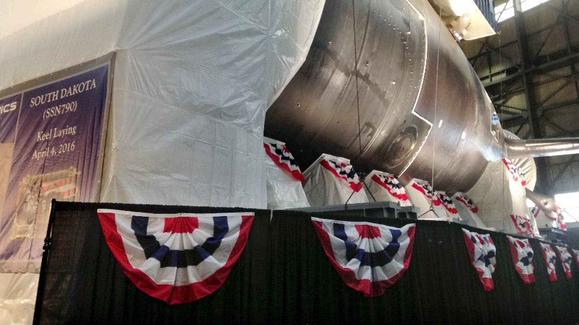 A module of the stern section of the nation's 17th Virginia-class attack submarine South Dakota is visible behind a backdrop during a ceremony at the manufacturing plant for General Dynamics' Electric Boat Monday, April 4, 2016, in North Kingstown, R.I. The keel of the nation's 17th Virginia-class attack submarine named for South Dakota is being laid at the manufacturing plant for General Dynamics' Electric Boat. The submarine doesn't have a traditional keel running the length of the ship, but is built in modules. (AP Photo/Jennifer McDermott)