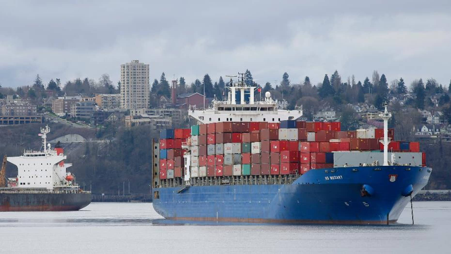 FILE - In this Feb. 20, 2015 file photo, the HS Mozart cargo ship, right, operated by the German shipping company Hansa Shipping, sits anchored in Commencement Bay near the Port of Tacoma, Wash. The Commerce Department reports on the U.S. trade gap for July on Thursday, Sept. 3, 2015. (AP Photo/Ted S. Warren, File)