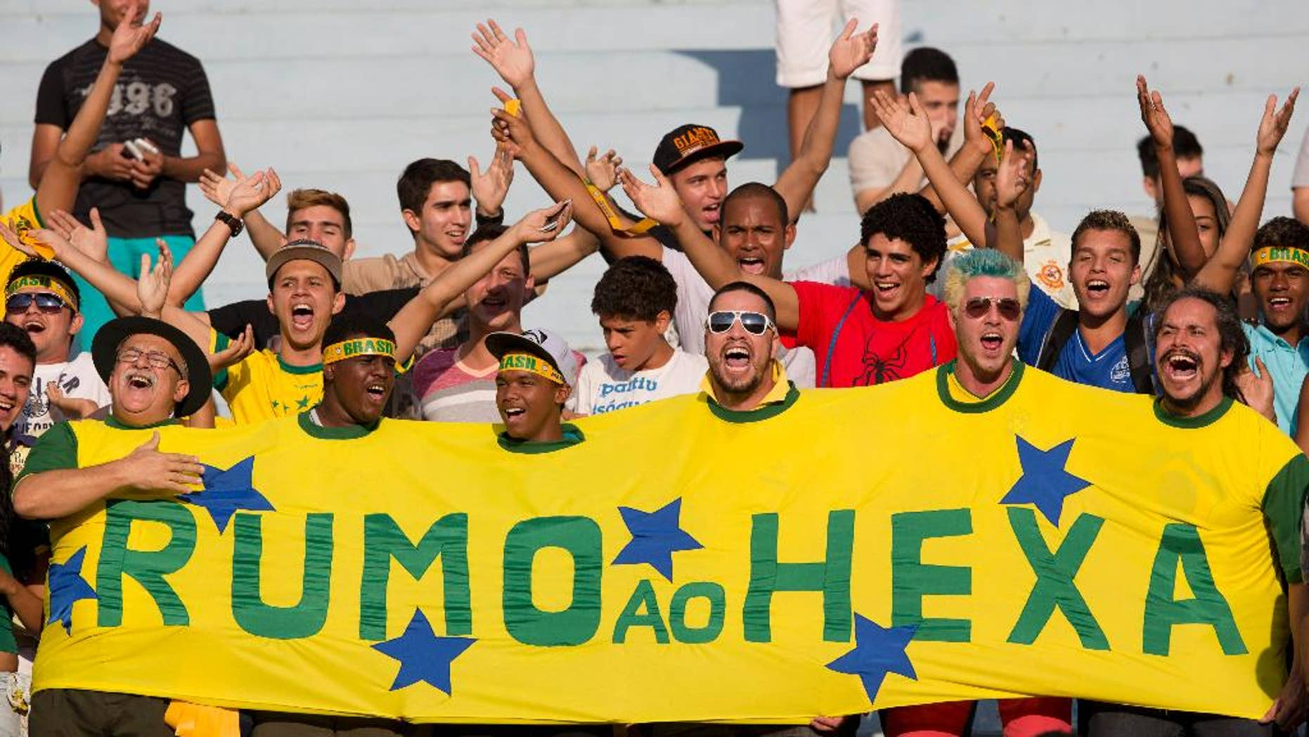 """Brazil's supporters cheer in the stands during a team practice session at the Serra Dourada stadium in Goiania, Brazil, Monday, June 2, 2014. The banner reads in Portuguese """"On its way to the sixth"""", referring to Brazil's five past World Cup titles and hope for a sixth this year. Brazil will face Panama on Tuesday in preparation for the World Cup soccer tournament that starts on 12 June. (AP Photo/Andre Penner)"""